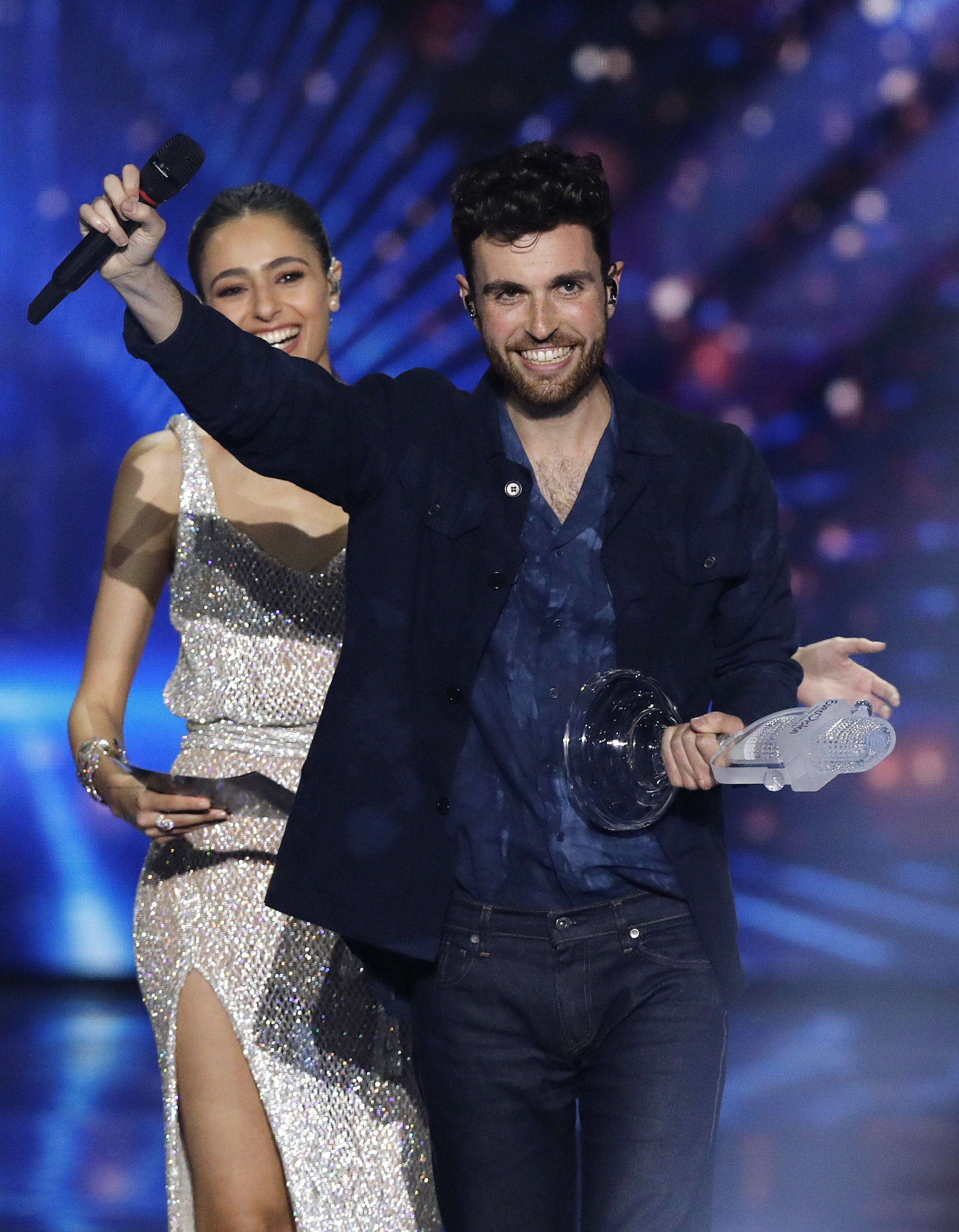 """Duncan Laurence of the Netherlands is watched by presenter Lucy Ayoub, left, as he holds the trophy after winning the 2019 Eurovision Song Contest grand final with the song """"Arcade"""" in Tel Aviv, May 18, 2019."""