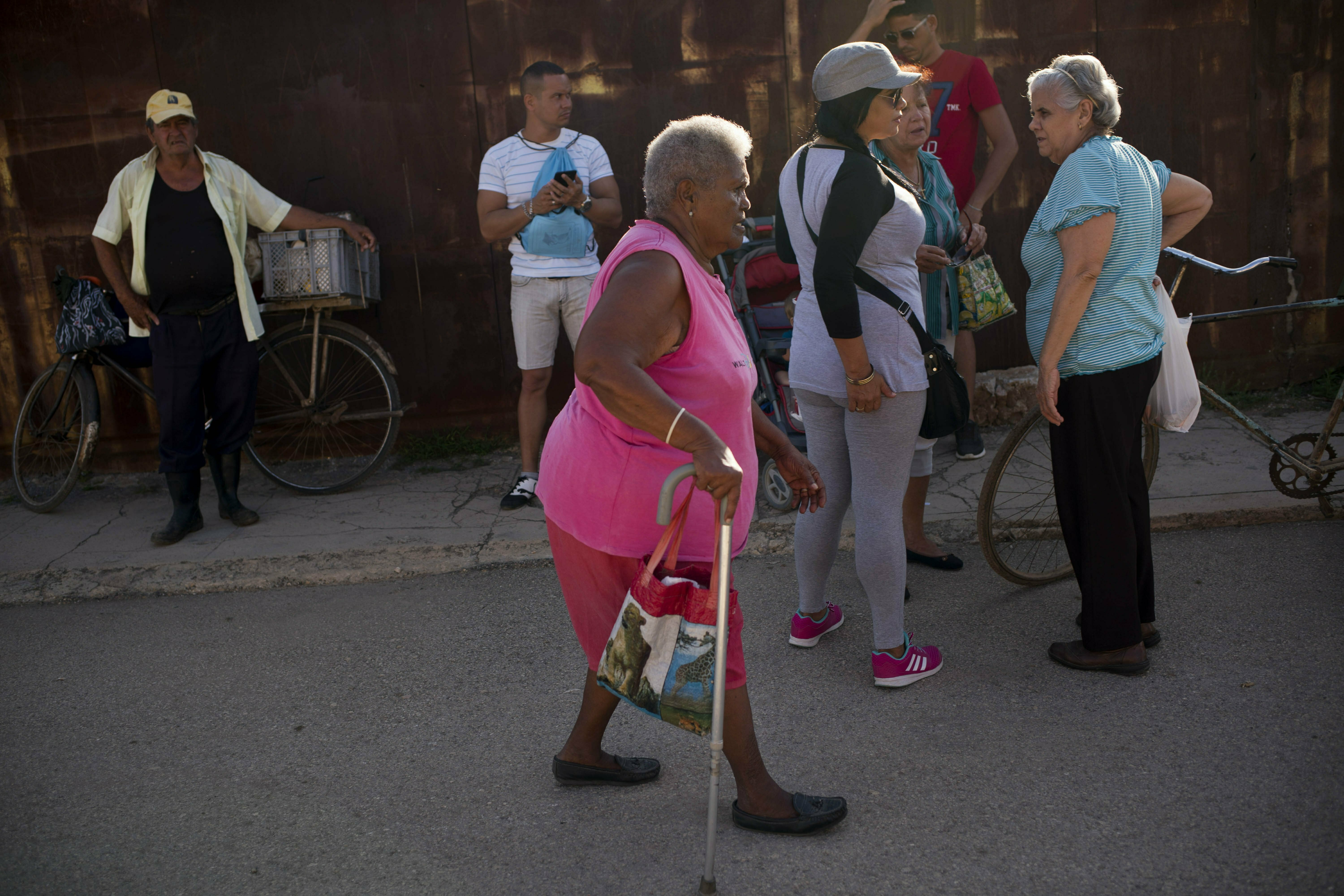 FILE - Pura Castell walks to a government-run butcher shop to buy chicken, after failing to find chicken the previous day, in Bauta, Cuba, April 12, 2019. A neighbor informed her that chicken had arrived at the government store that distributes almos...