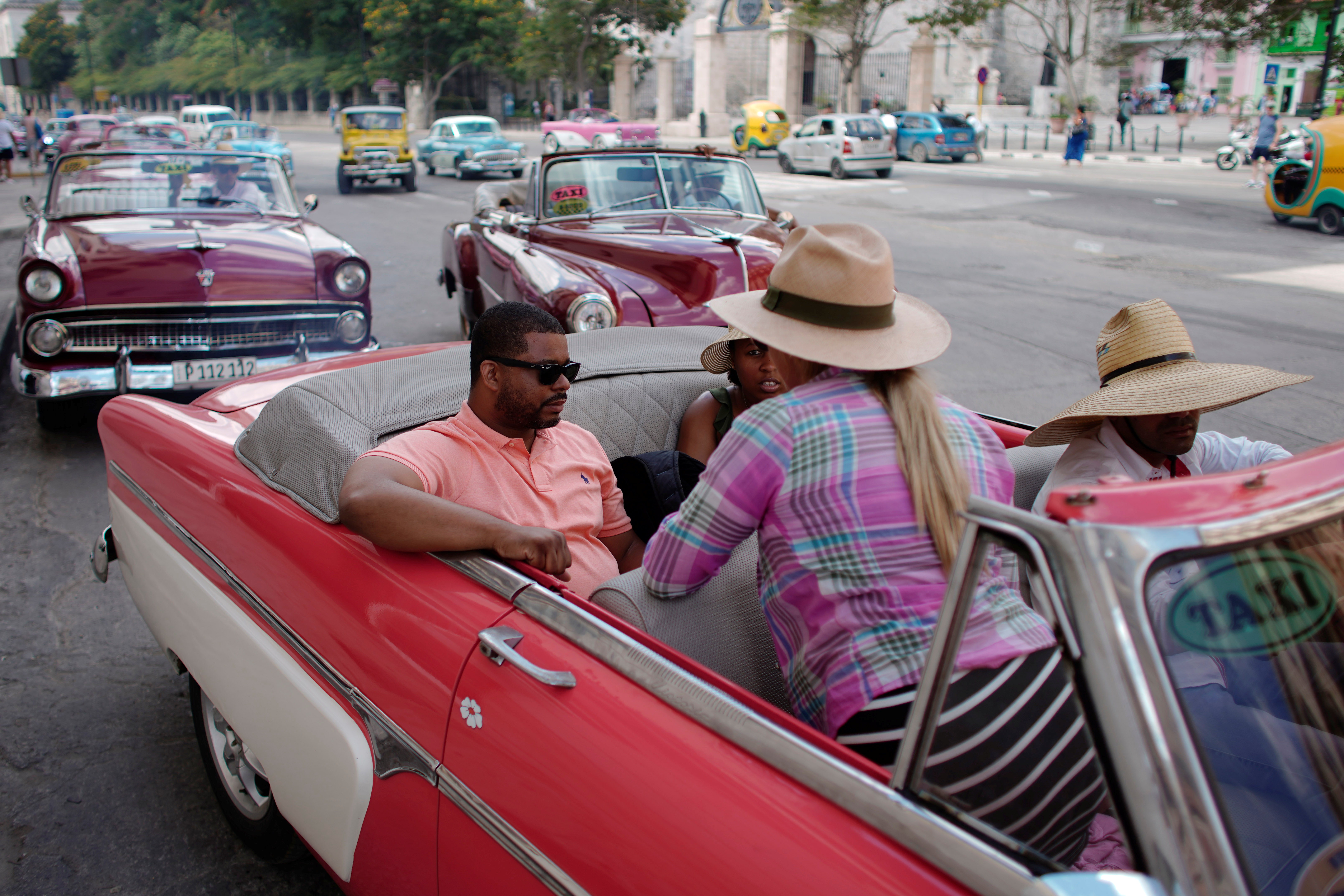 U.S. cruise ship tourists Aloyosius Howard and Kenyatta Puckett talk to a tour guide as they prepare to ride in a vintage car in Havana, Cuba, June 5, 2019.