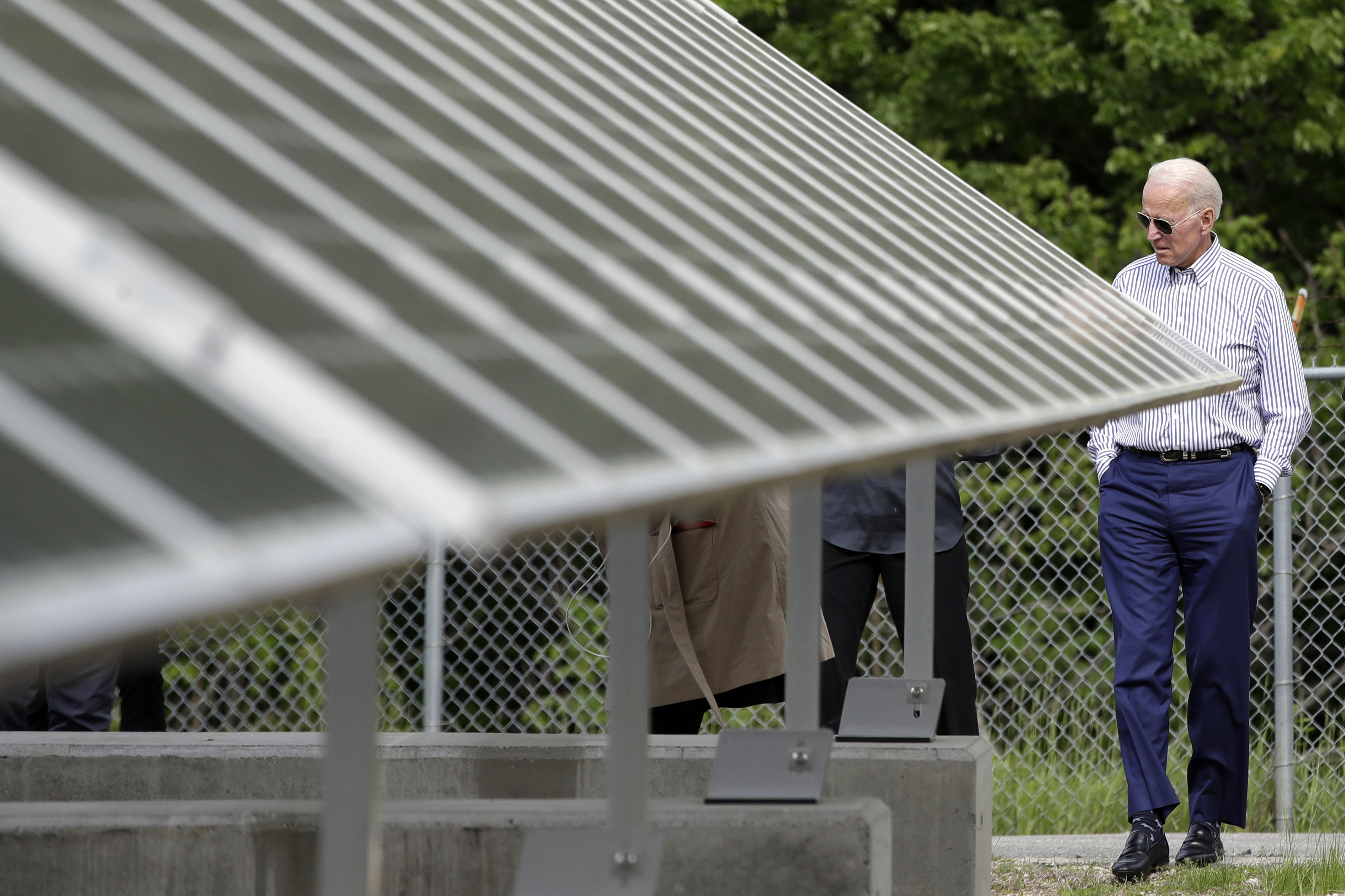 Former vice president and Democratic presidential candidate Joe Biden looks at an array of solar panels during a tour at the Plymouth Area Renewable Energy Initiative in Plymouth, N.H., June 4, 2019.