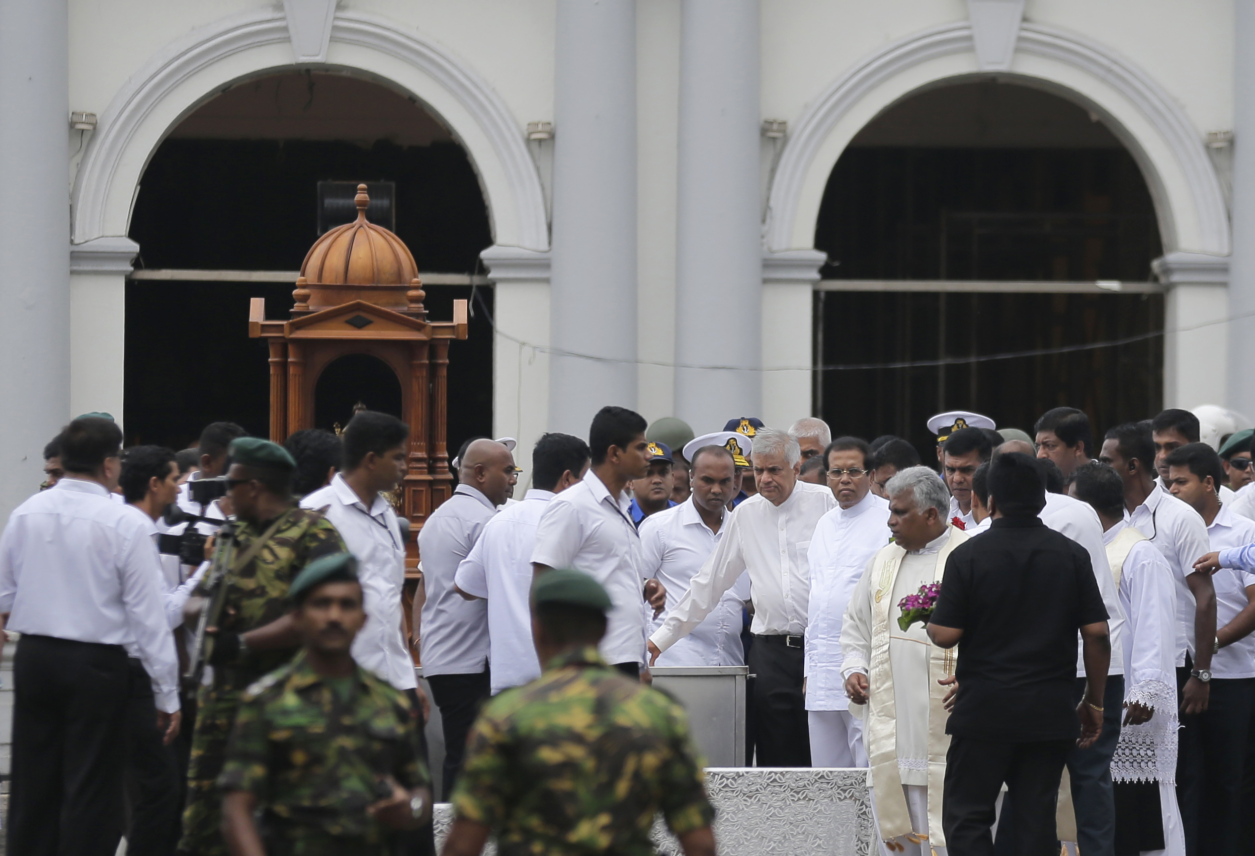 Sri Lankan President Maithripala Sirisena and Prime Minister Ranil Wickremasinghe, facing camera at right, attend a brief holy service marking the seventh day of the Easter attacks outside St. Anthony's Church in Colombo, Sri Lanka, April 28, 2019.