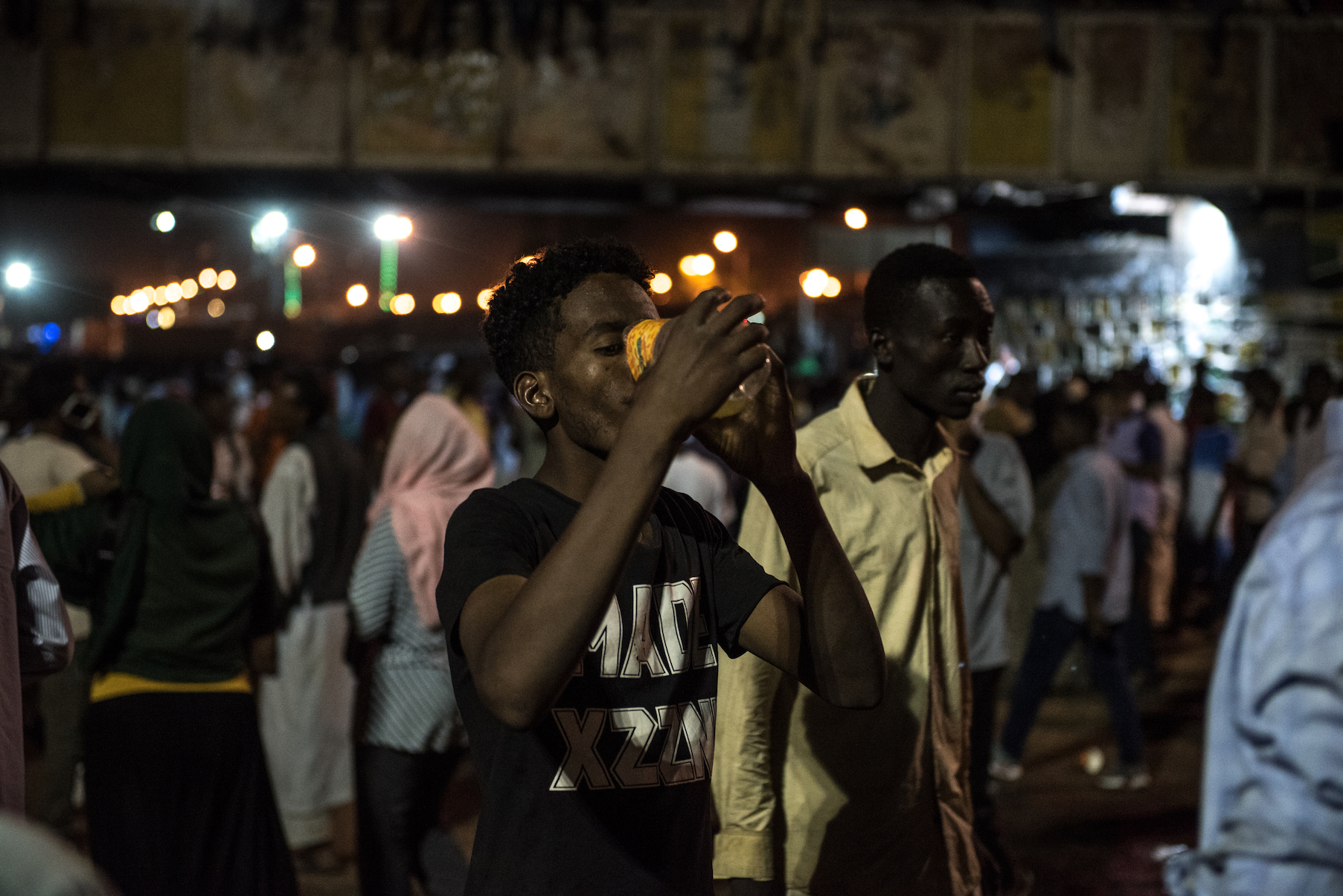 A young man drinks juice to hydrate himself on the first night of Ramadan after iftar on May 6, 2019, at the sit-in in Khartoum, Sudan.