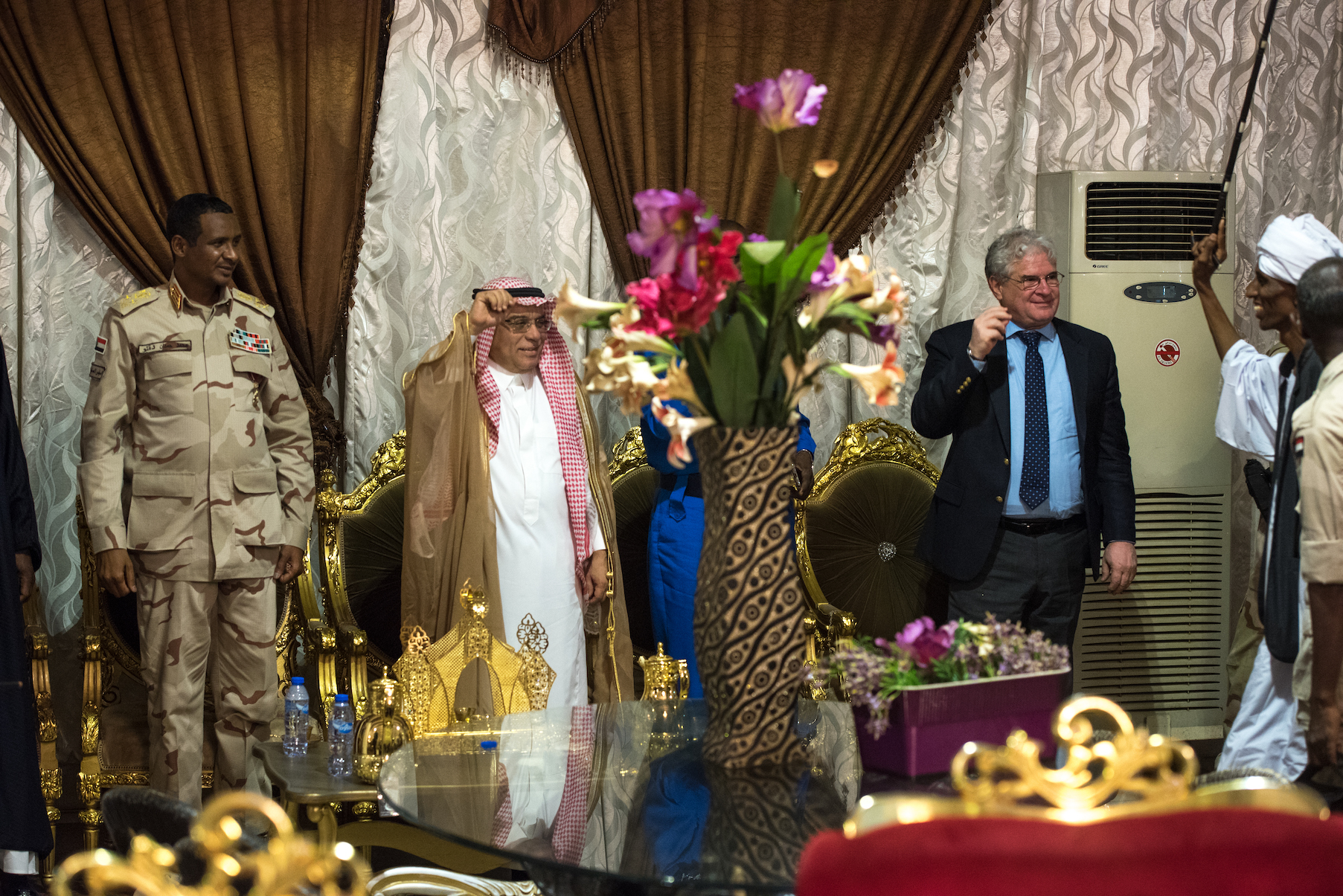 U.S. Charge d'Affaires to Sudan Steven Koutsis (right, in suit) snaps his fingers to music as guests gather for a dinner honoring militia commander Mohamed Hamdan Dagolo (far left). Also pictured is Saudi Ambassador to Sudan Sheikh Abdullah al Malhou...