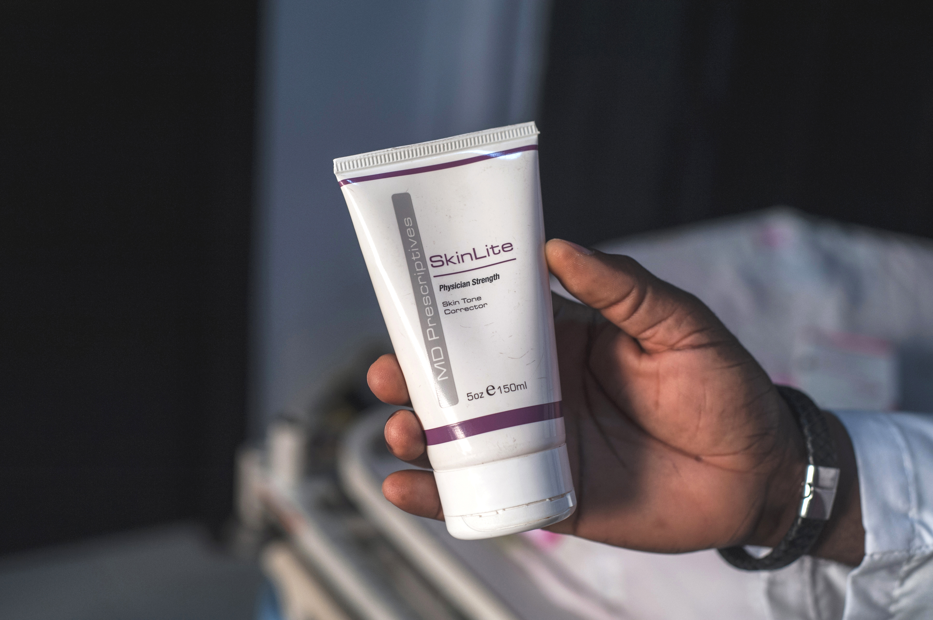Aranmolate Ayobami, plastic surgeon at Grandville Medical and Laser clinic in Lagos, Nigeria, holds a tube of Skinlite a skin lightening product used at his clinic, July 17, 2018, in Lagos.