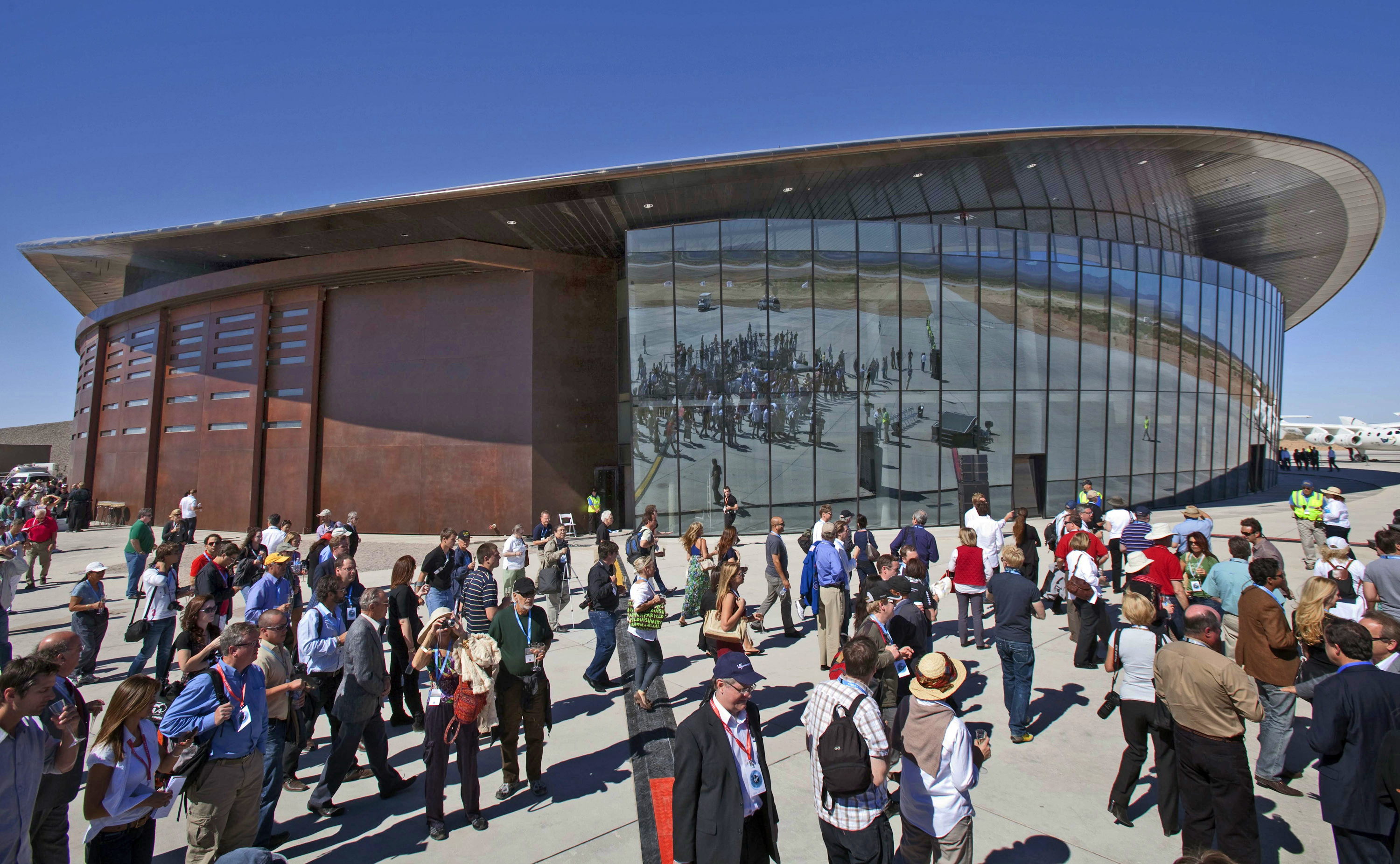 FILE - Guests stand outside the new Spaceport America hangar in Upham, N.M., Oct. 17, 2011. Operators of the New Mexico Spaceport Authority that runs Spaceport America are seeking greater confidentiality for tenants that include aspiring commercial s...