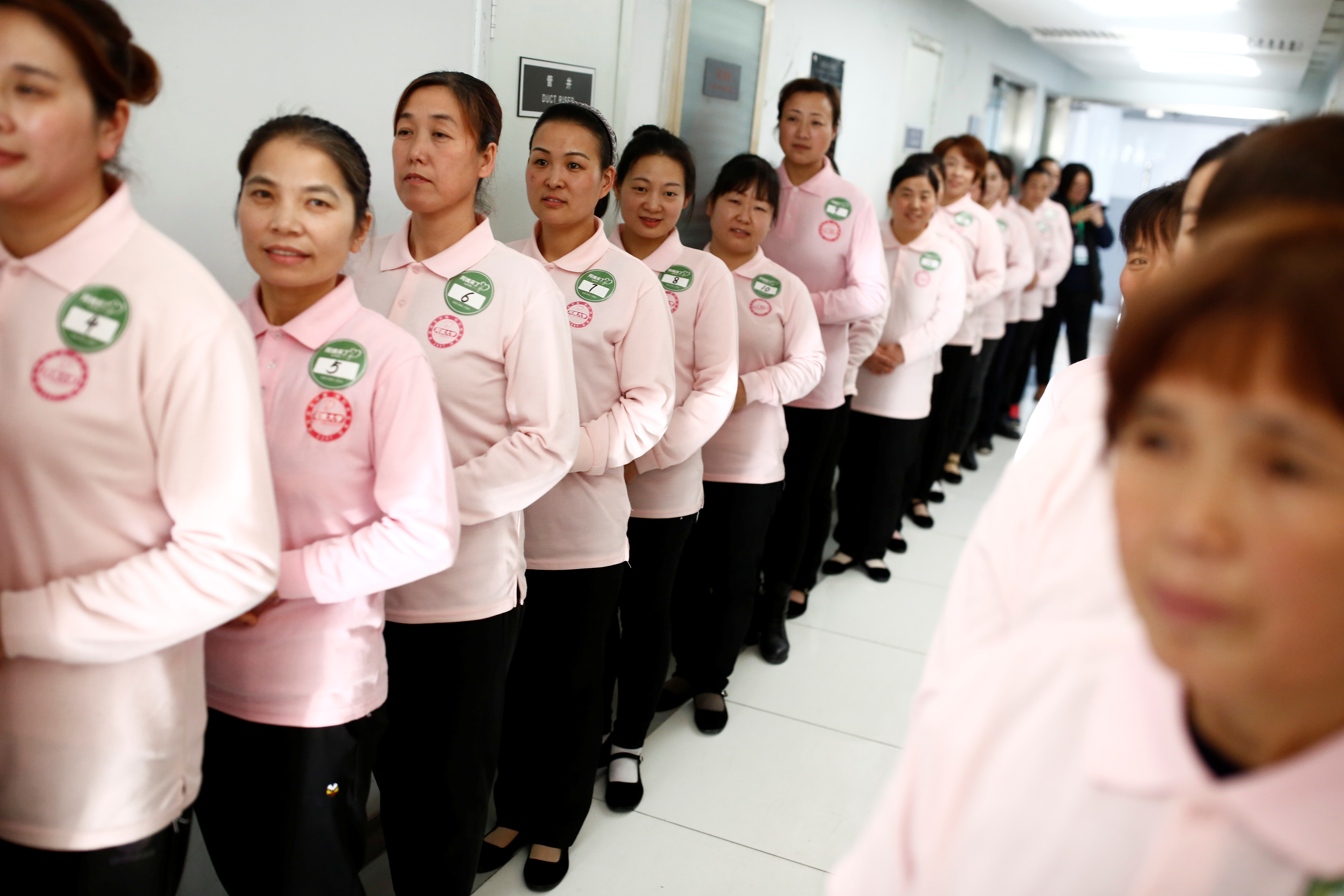 FILE - Graduates of Ayi University, a training program for domestic helpers, line up to meet potential employers in Beijing, China, Dec. 11, 2018.