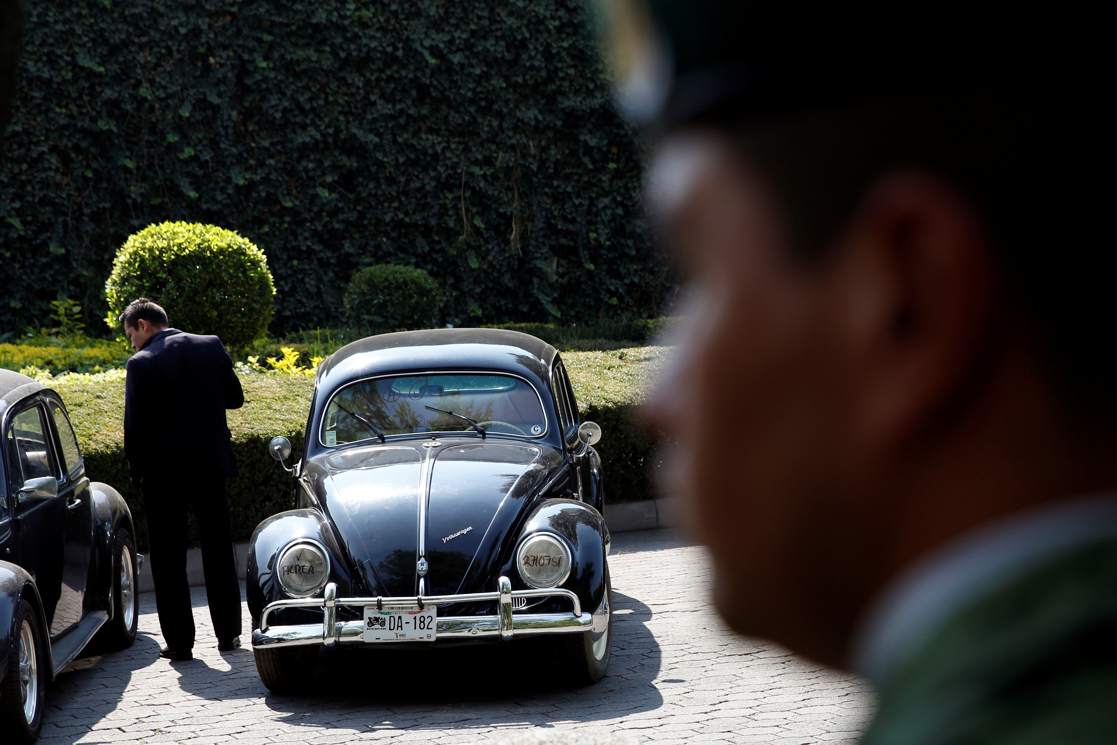 A man stands next to a 1951 Volkswagen, part of the fleet of vehicles seized by the government from politicians and organized crime as part of an auction in Mexico City, May 21, 2019.