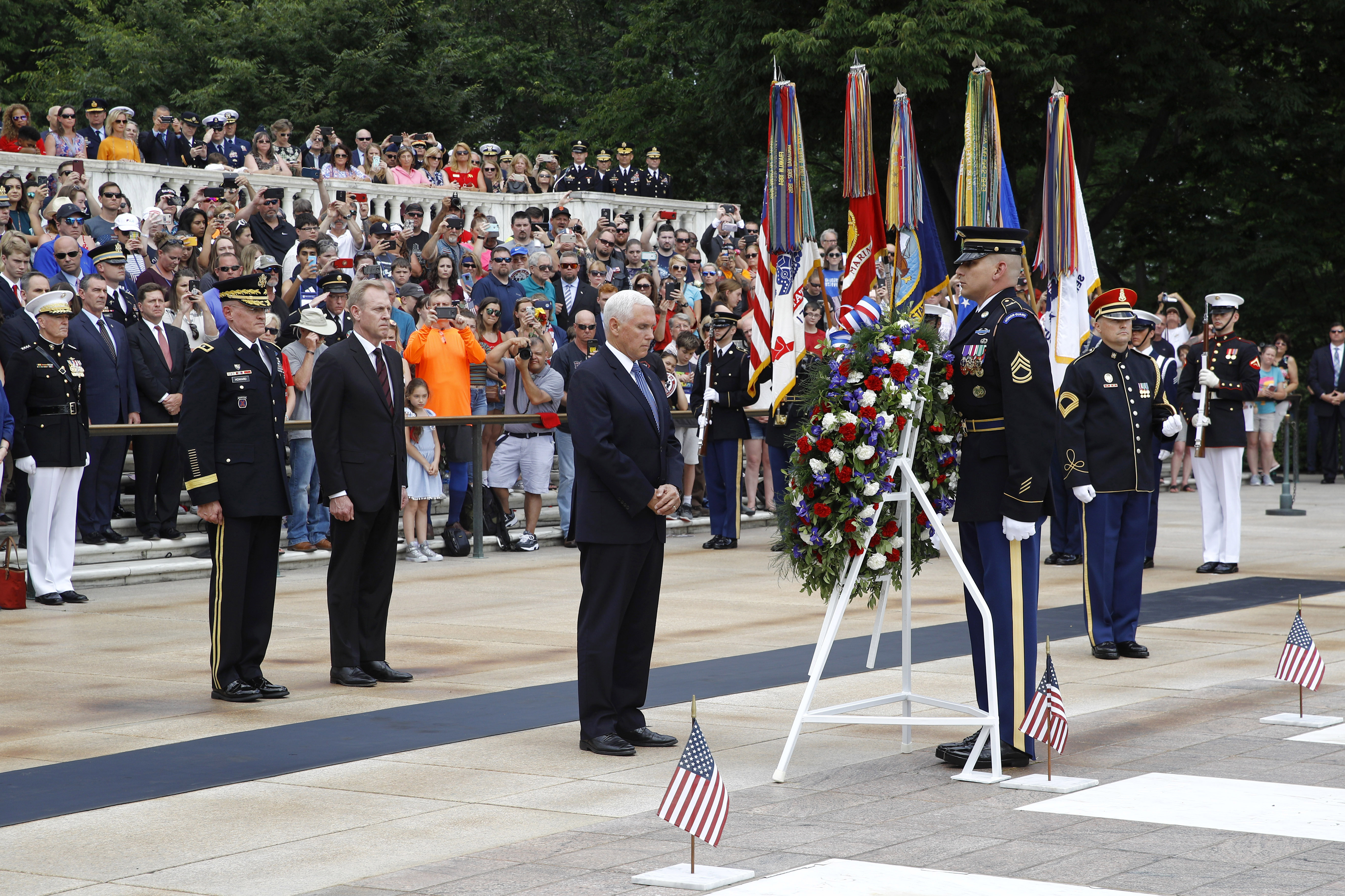 Vice President Mike Pence, center, pauses after placing a wreath in front of the Tomb of the Unknown Soldier in observance of Memorial Day, May 27, 2019, at Arlington National Cemetery in Arlington, Virginia.