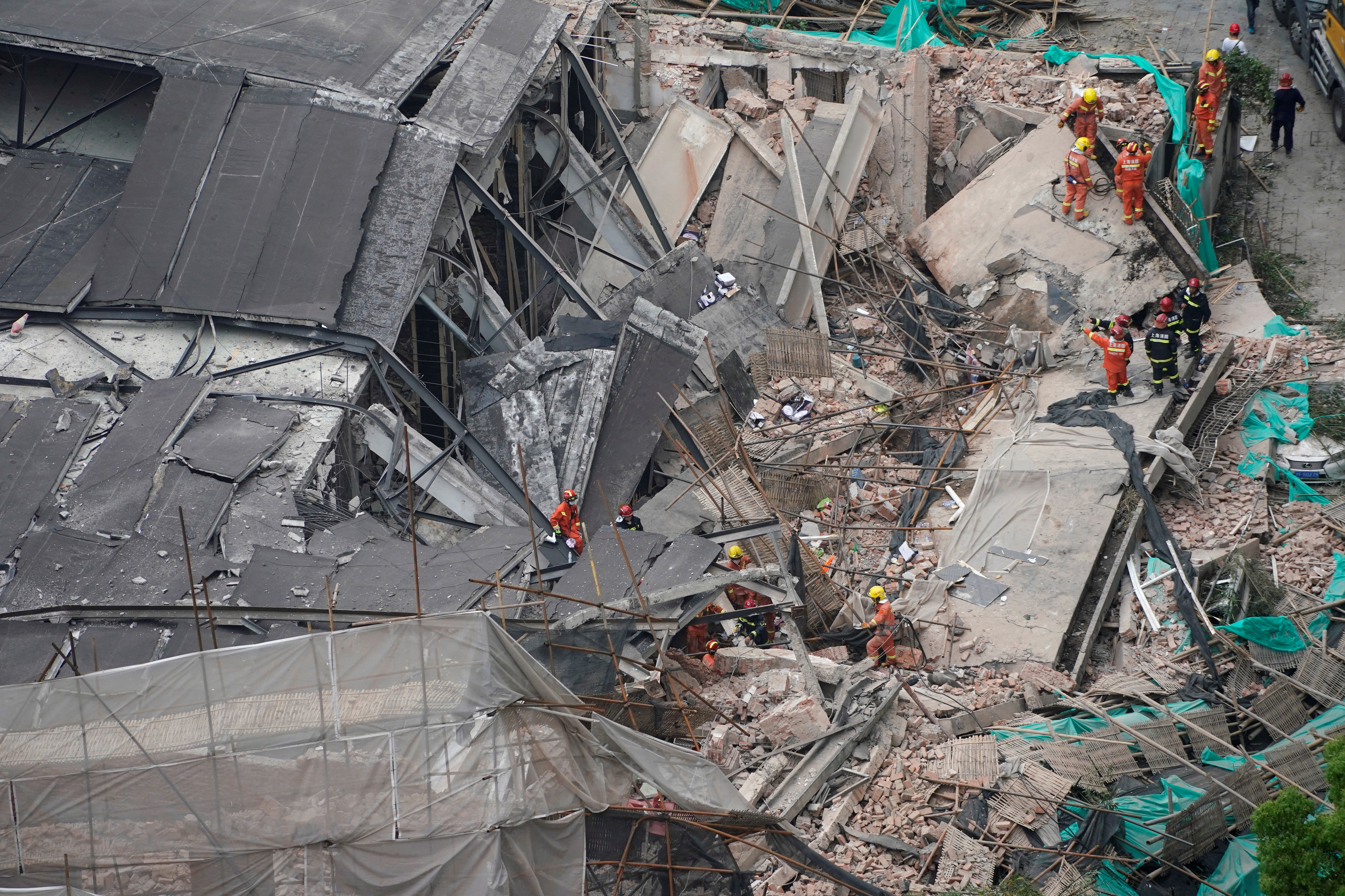 Firefighters work at the site where a building collapsed, in Shanghai, May 16, 2019.
