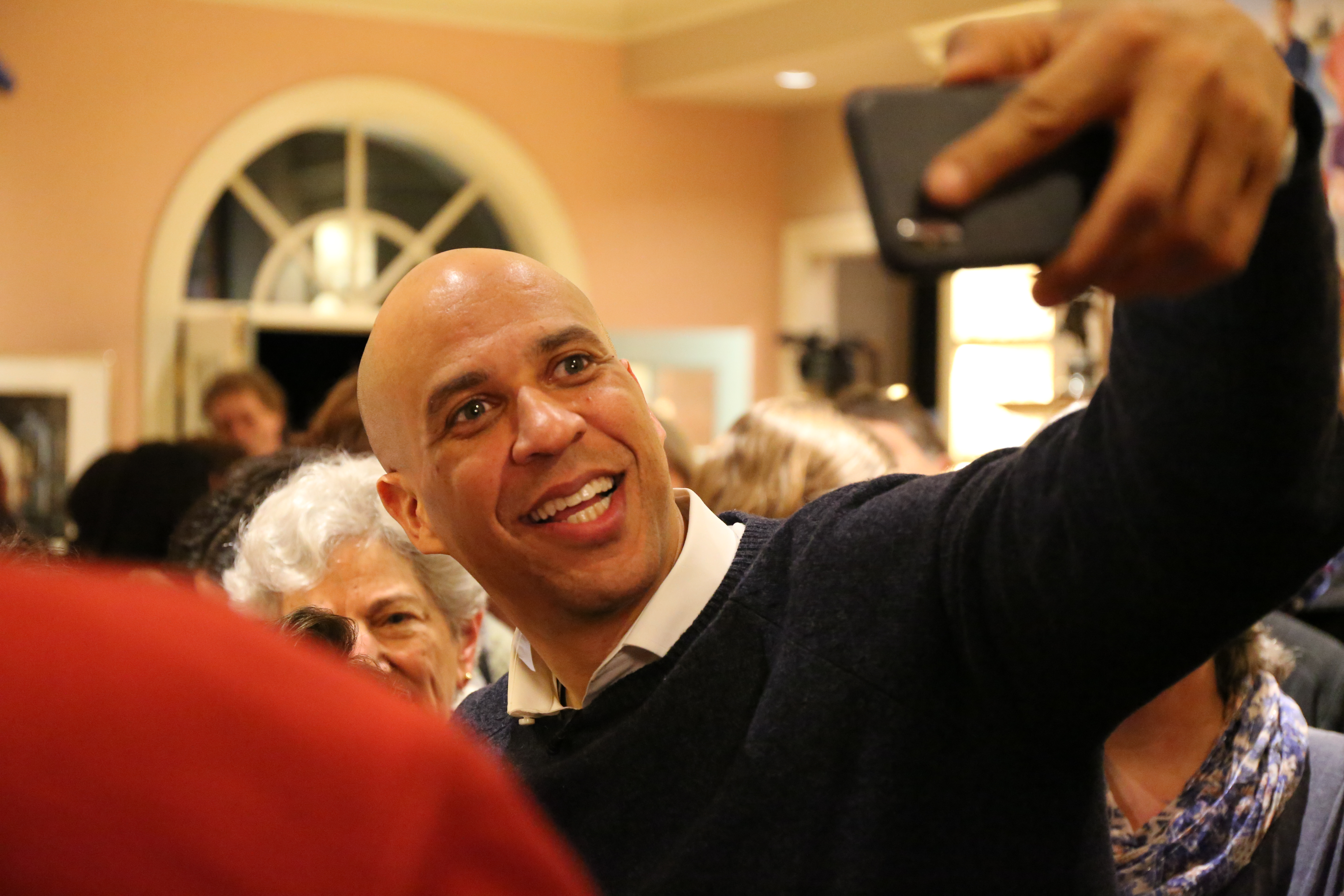 Senator Cory Booker of New Jersey takes selfies with voters at a New Hampshire house party.
