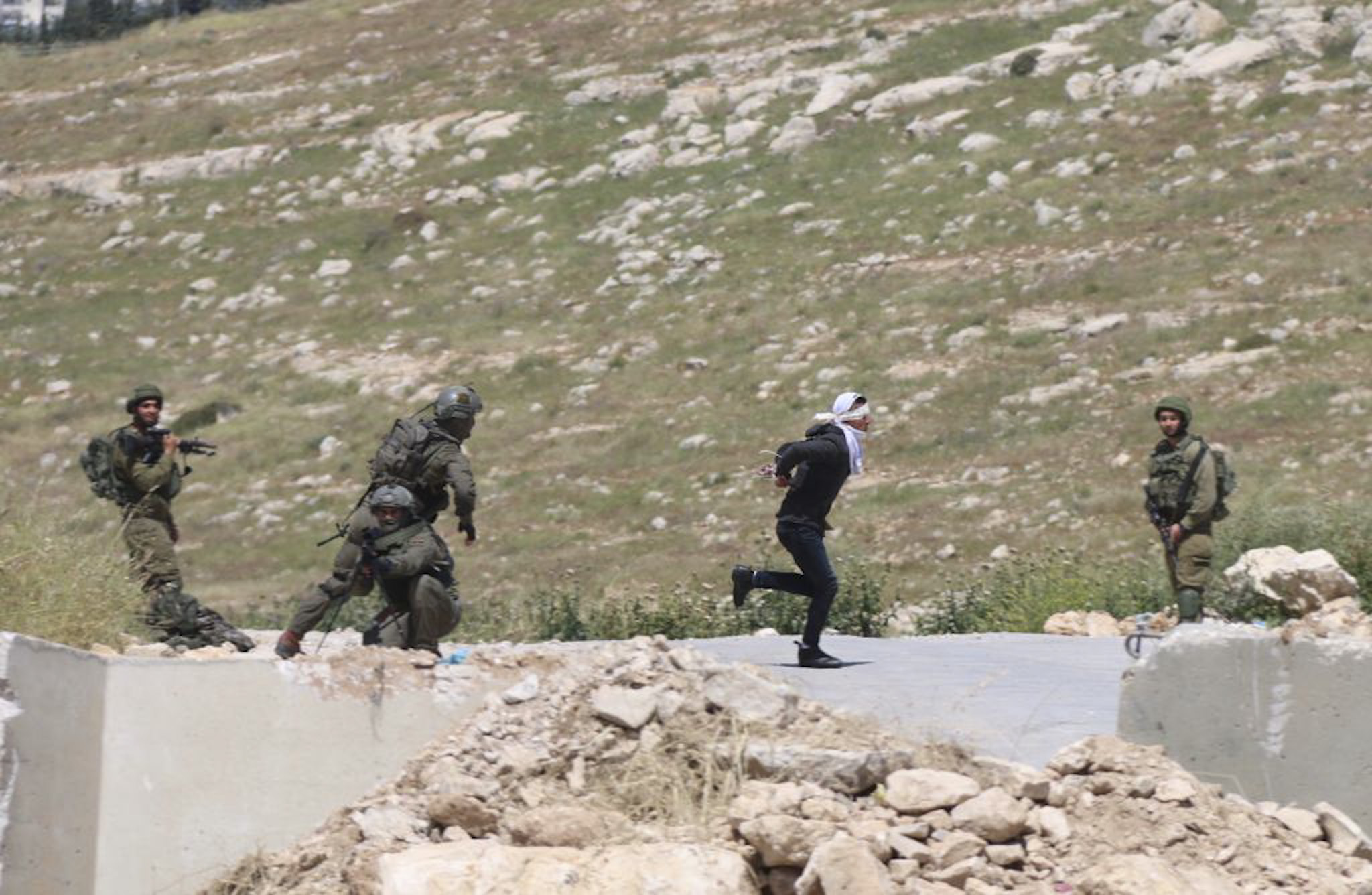 Handcuffed and blindfolded Osama Hajahjeh, 16, runs away from Israeli soldiers near the village of Tekoa, West Bank, Apri 18, 2019.