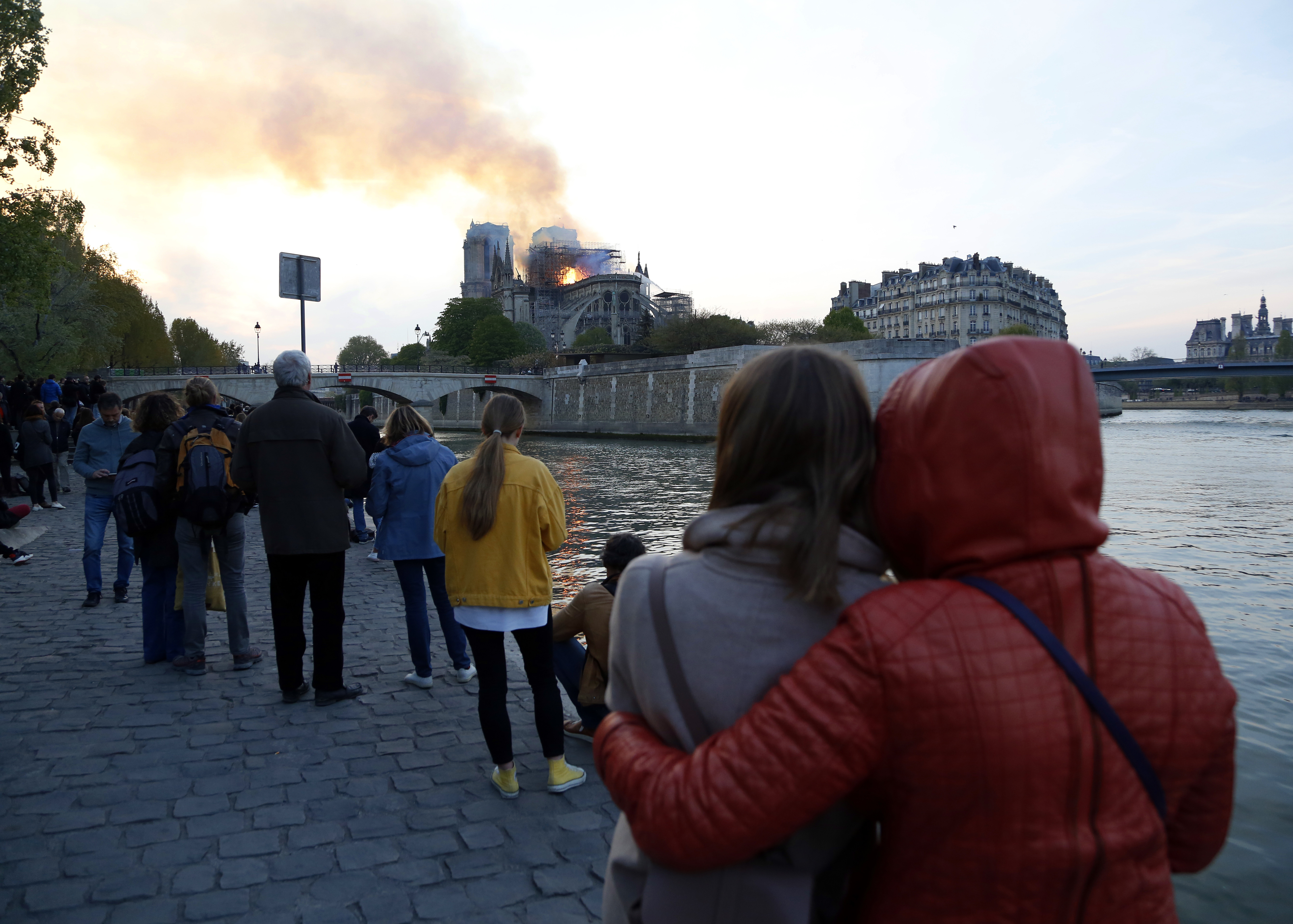 People watch as flames and smoke rise from Notre Dame cathedral as it burns in Paris, Monday, April 15, 2019.