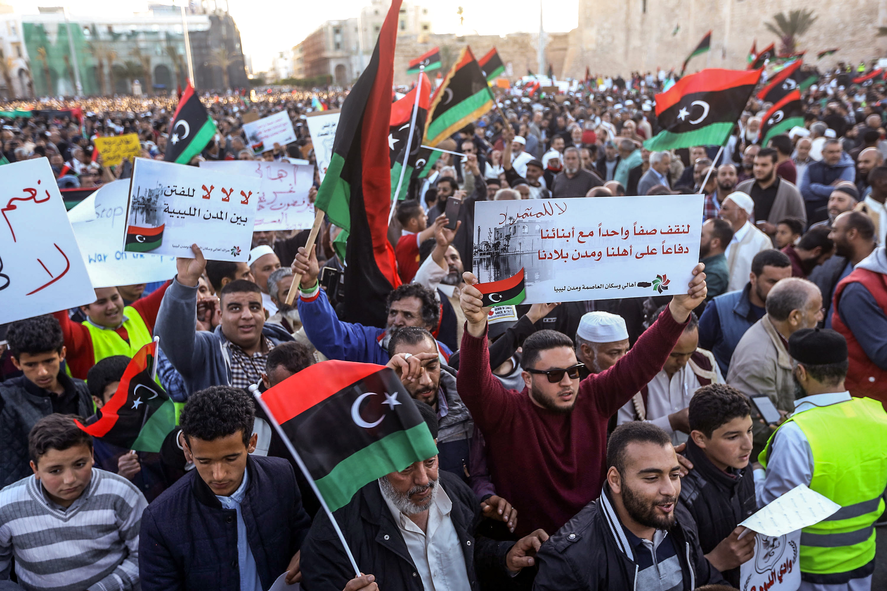 Libyans wave national flags and chant slogans during a demonstration against strongman Khalifa Haftar in Martyrs Square, Tripoli, April 12, 2019.