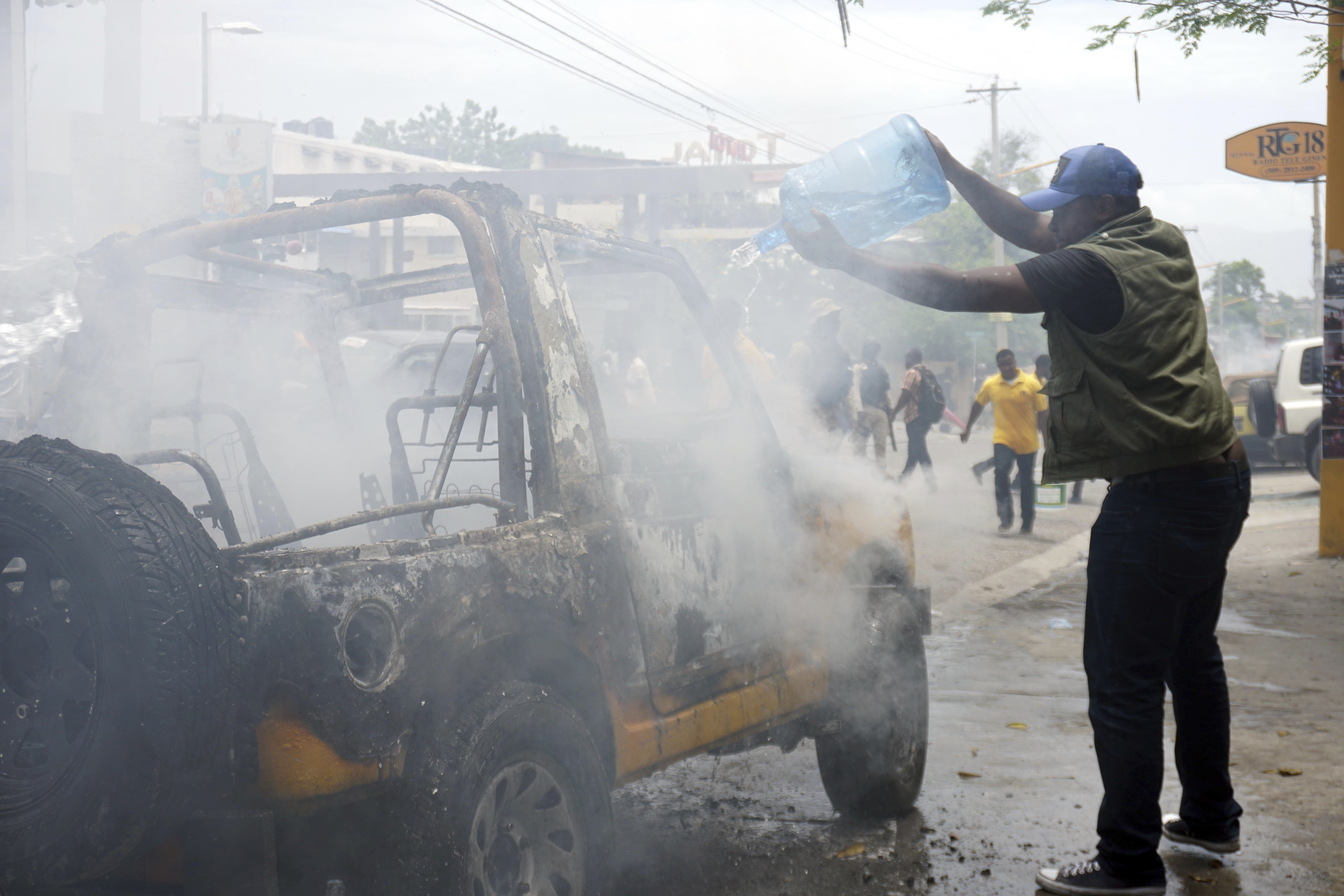 Journalist throws water on burning vehicle in Port au Prince