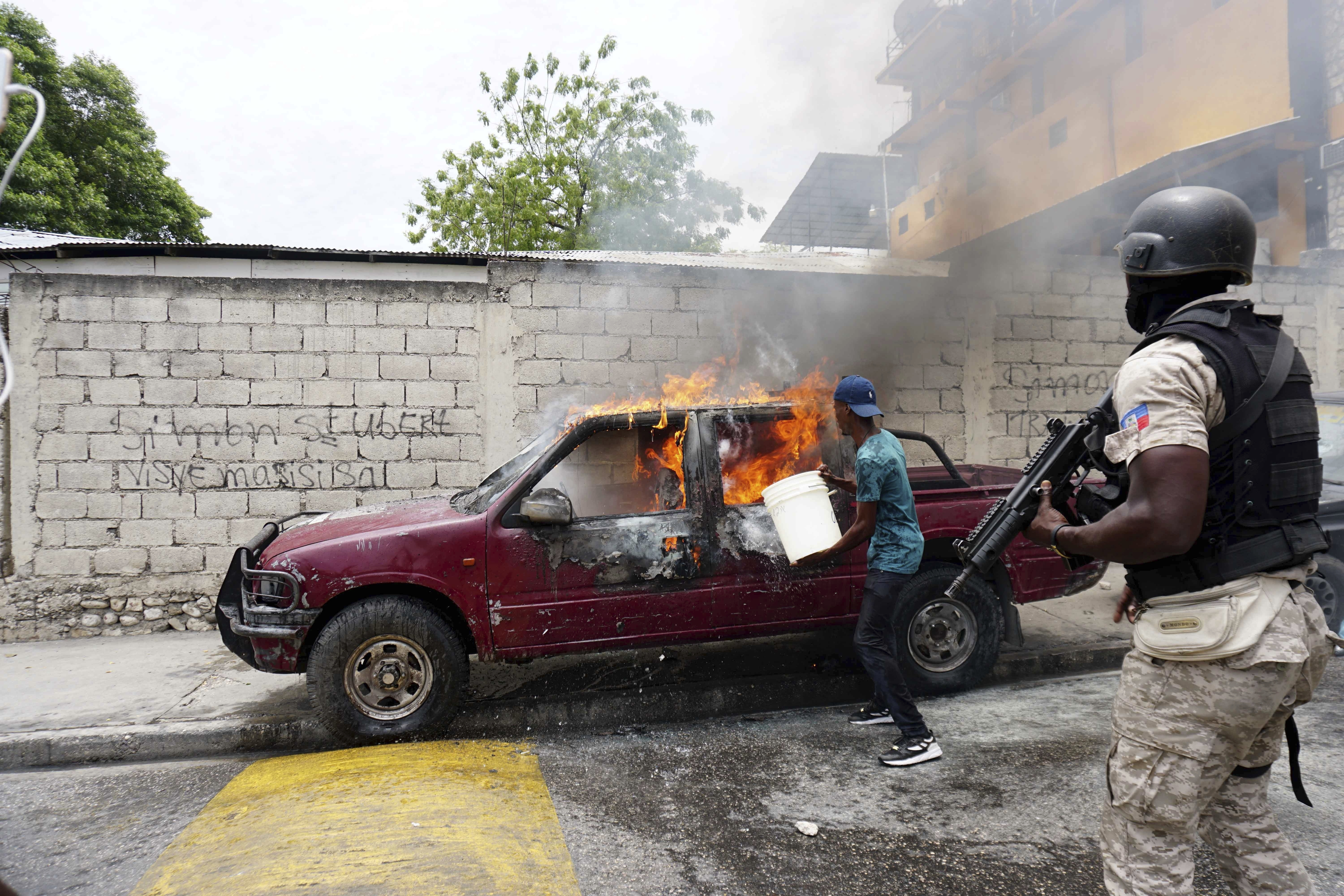 Haitian Policeman stands guard as man attempts to put out fire