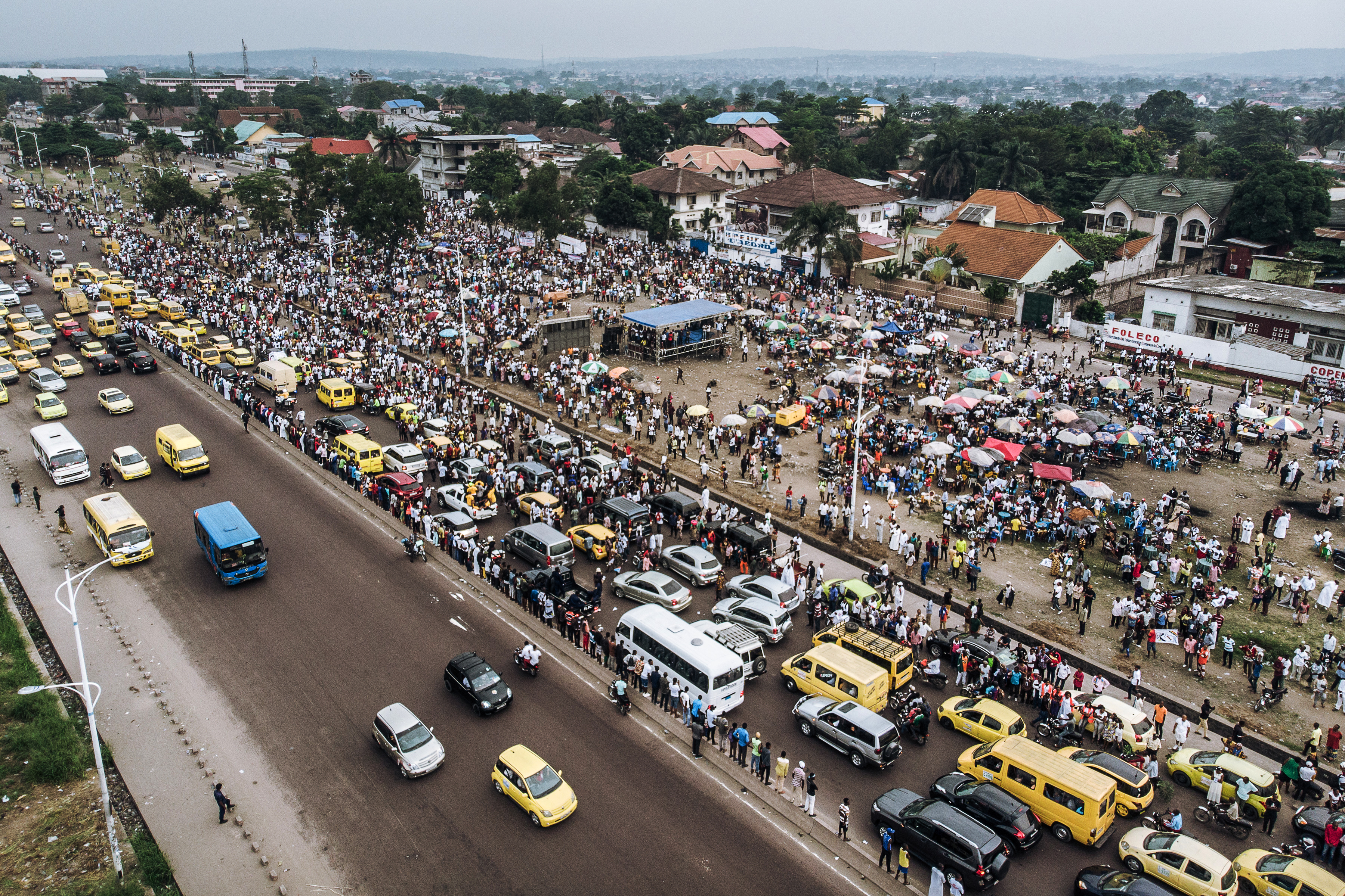 An aerial view shows a crowd gathered outside the Union for Democracy and Social Progress (UDPS) headquarters in the Limete neighborhood of Kinshasa, May 30, 2019, as party supporters await the return of the remains of former Congolese Prime Minister...