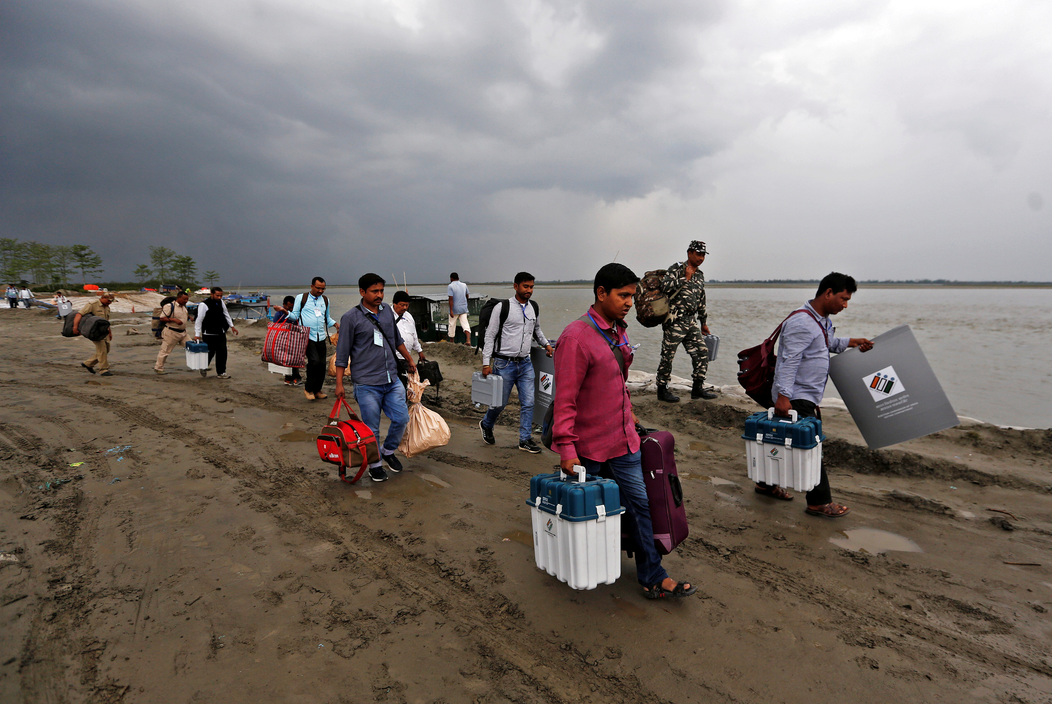 Polling officers carry electronic voting machine (EVM) towards their vehicles after arriving on a ferryboat in Nimatighat, Jorhat district, in the northeastern Indian state of Assam, India, Apr. 9, 2019.