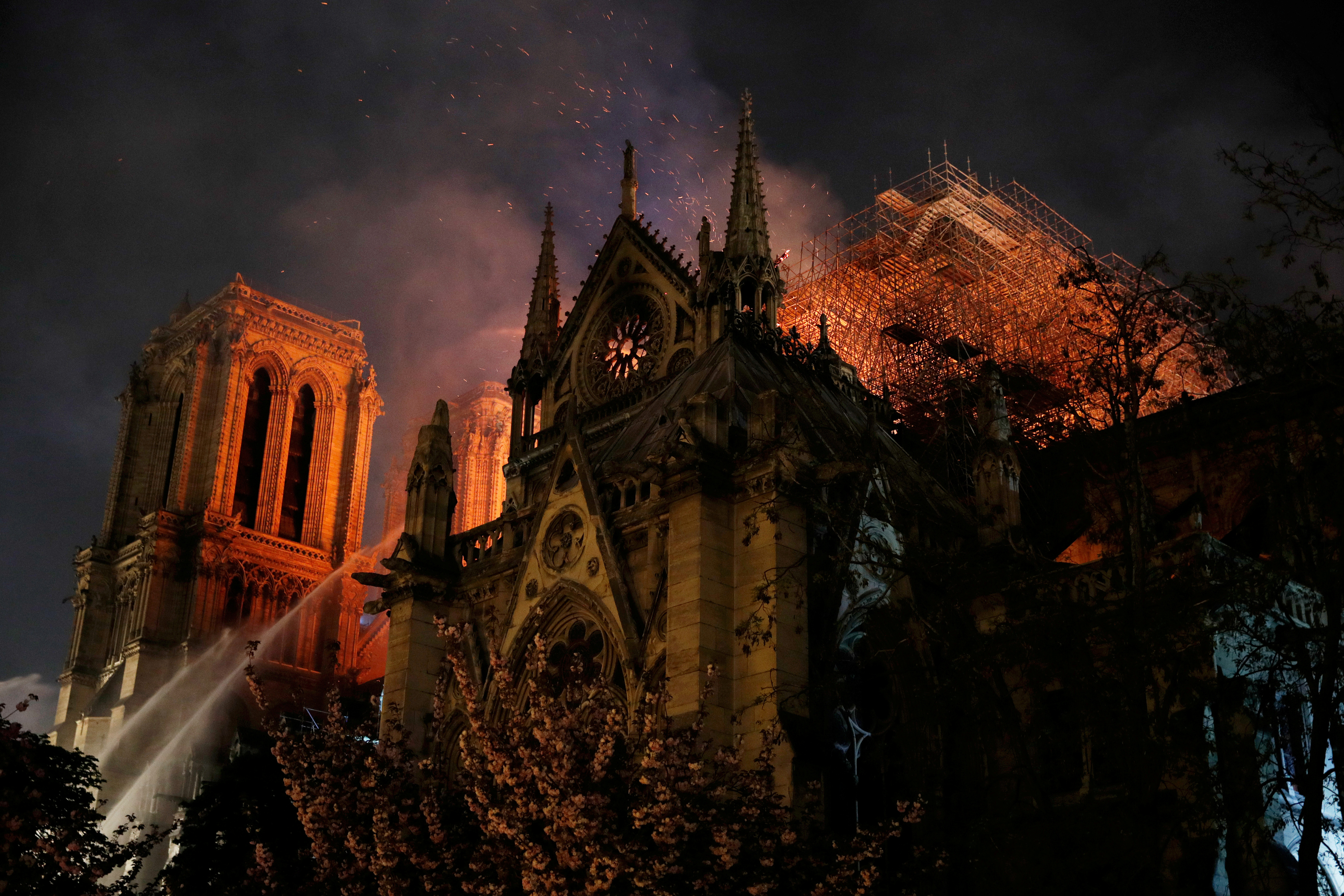Sparks fill the air as Paris Fire brigade members spray water to extinguish flames as the Notre Dame Cathedral burns in Paris,  April 15, 2019.