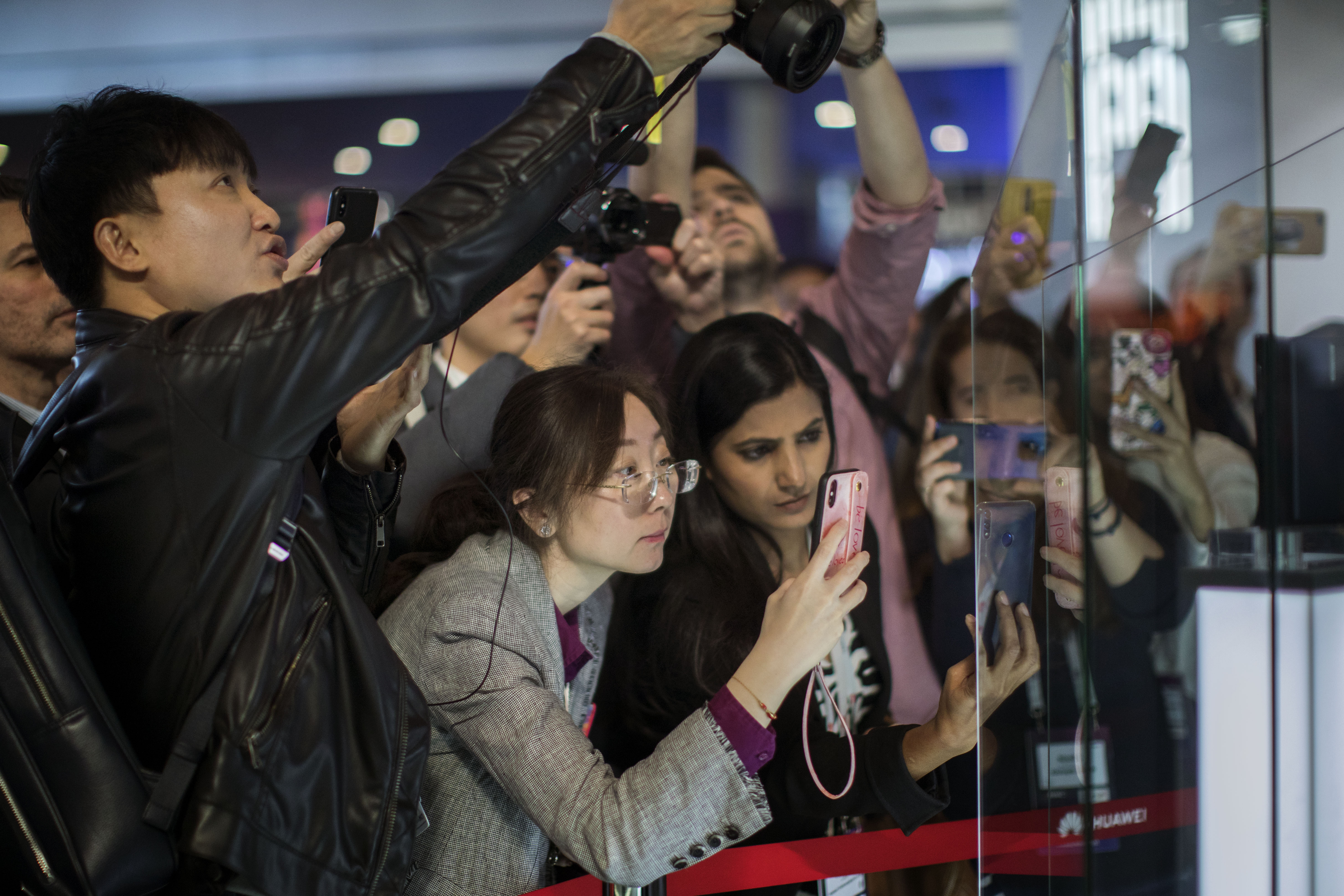 Attendees take pictures of the new Huawei Mate X foldable 5G smartphone during the Mobile World Congress wireless show, in Barcelona, Spain, Monday, Feb. 25, 2019.  (AP Photo/Emilio Morenatti)