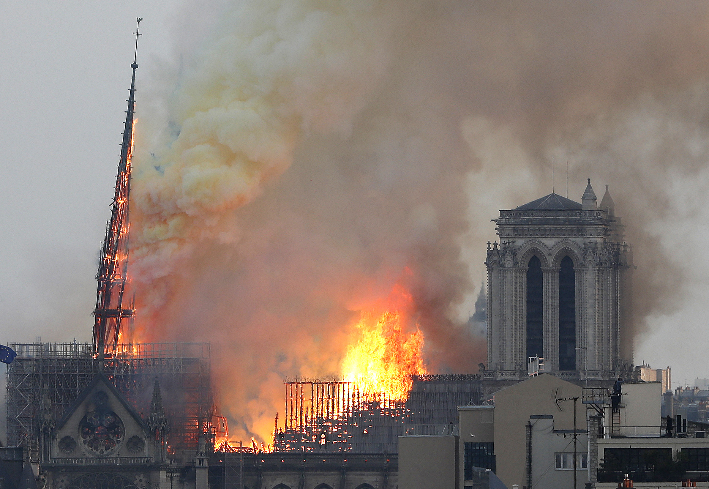 Flames rise from Notre Dame cathedral as it burns in Paris, Monday, April 15, 2019. Massive plumes of yellow brown smoke is filling the air above Notre Dame Cathedral and ash is falling on tourists and others around the island that marks the center o...