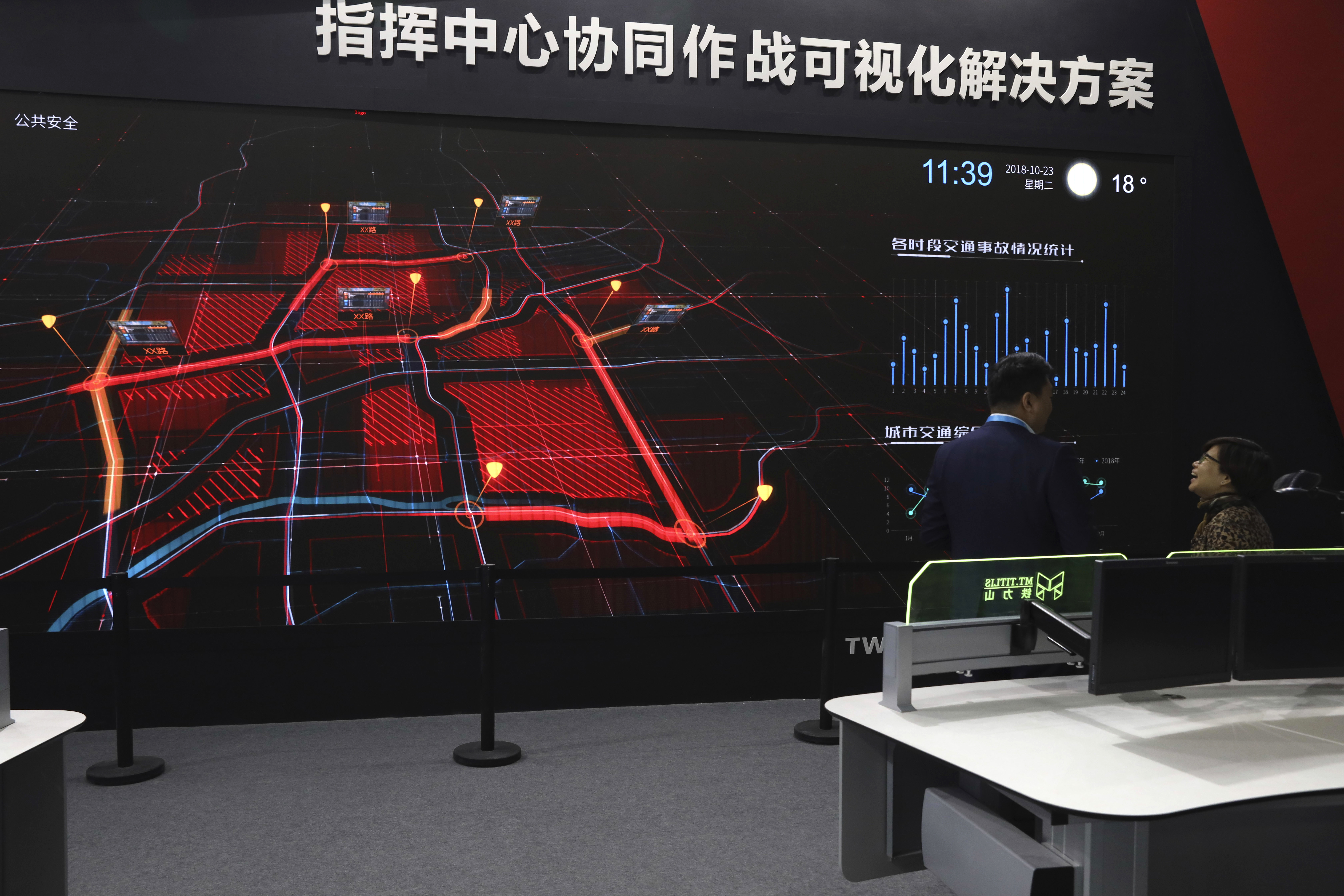 FILE - A visitor is briefed on a screen demonstrating city level surveillance at Security China 2018 expo in Beijing, Oct. 23, 2018.