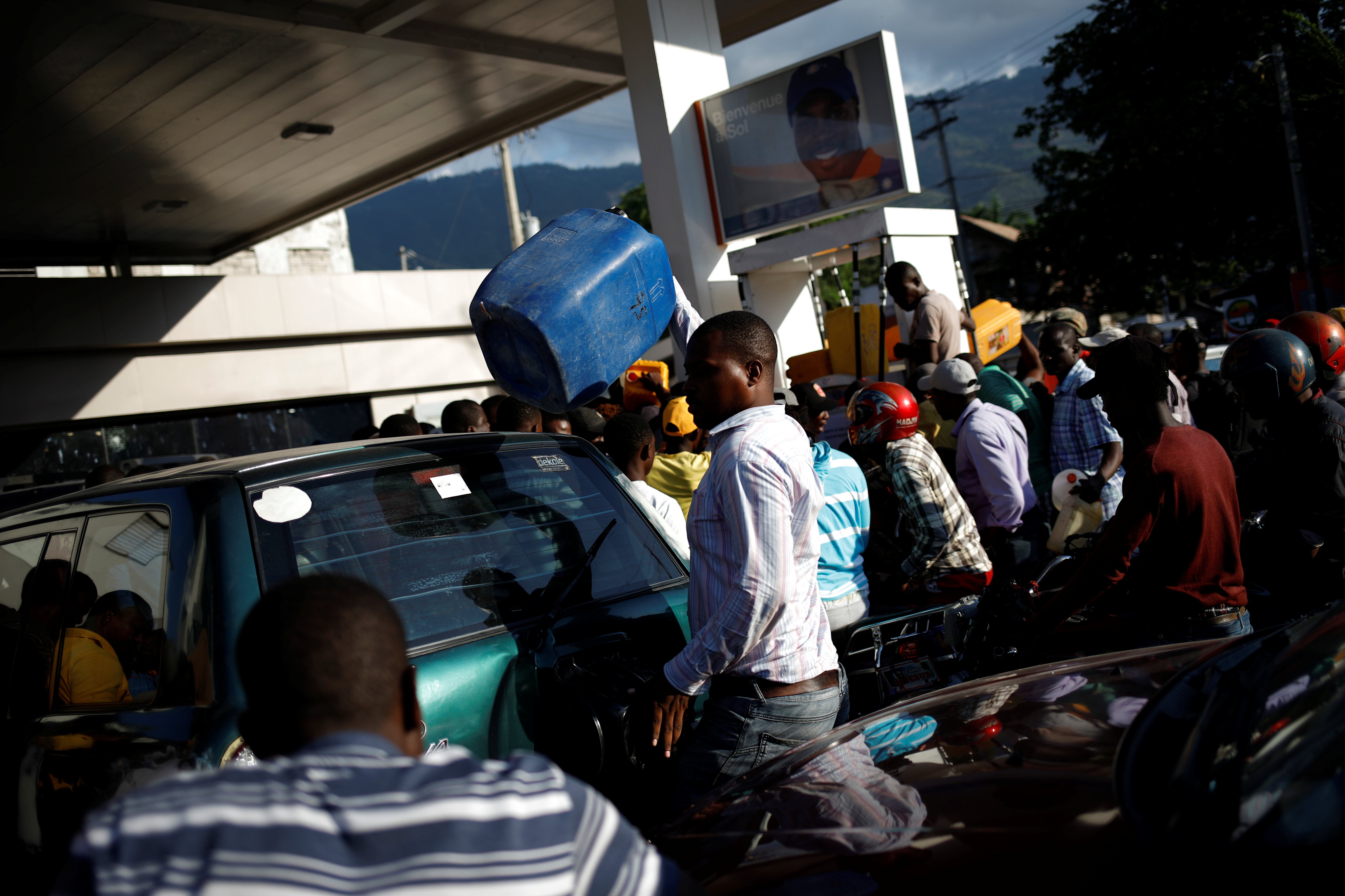 Motorbike riders and car drivers wait to get fuel at a gas station in Port-au-Prince, Haiti, April 4, 2019.