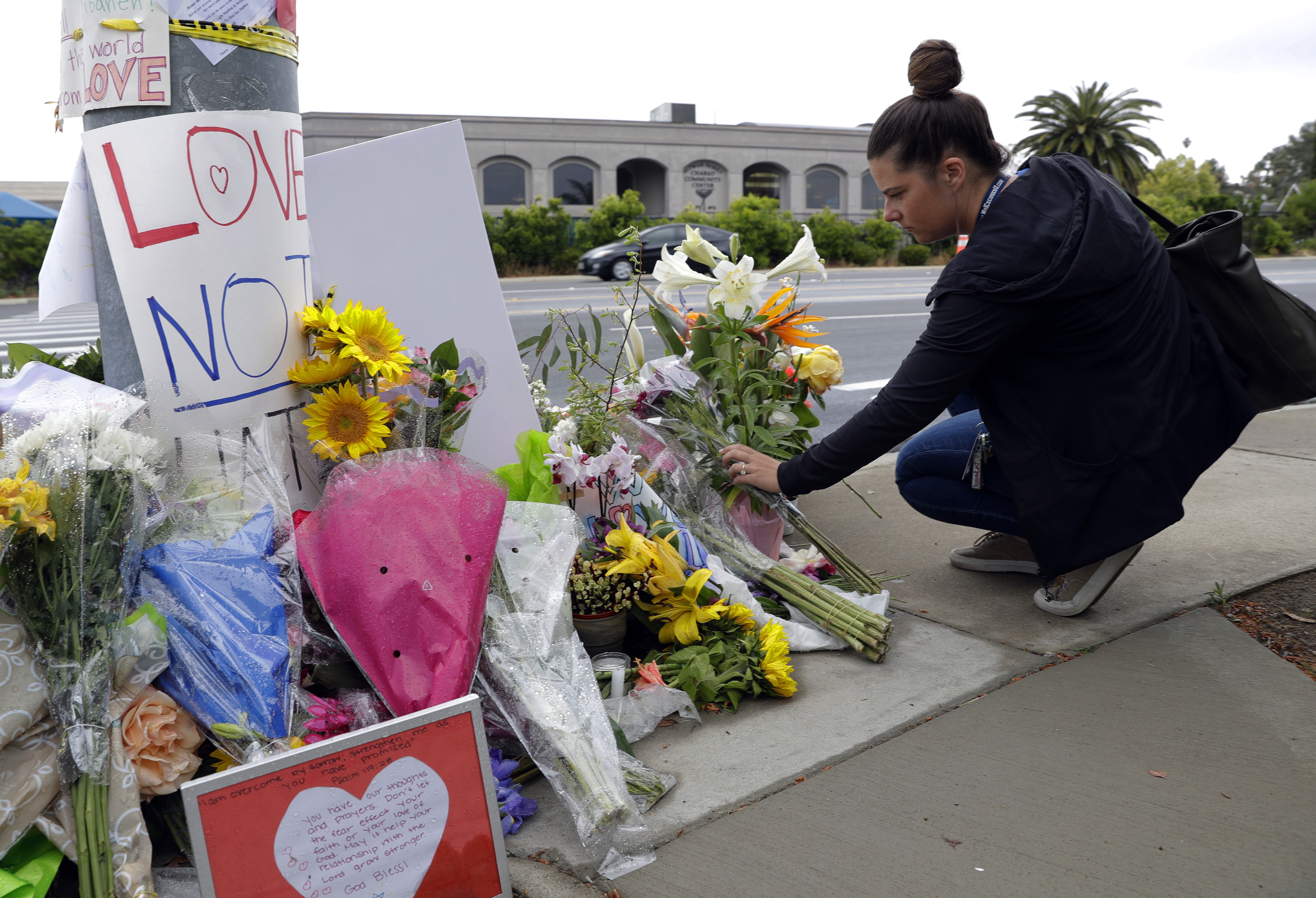 A woman leaves flowers on a growing memorial across the street from the Chabad of Poway synagogue in Poway, California, April 29, 2019.