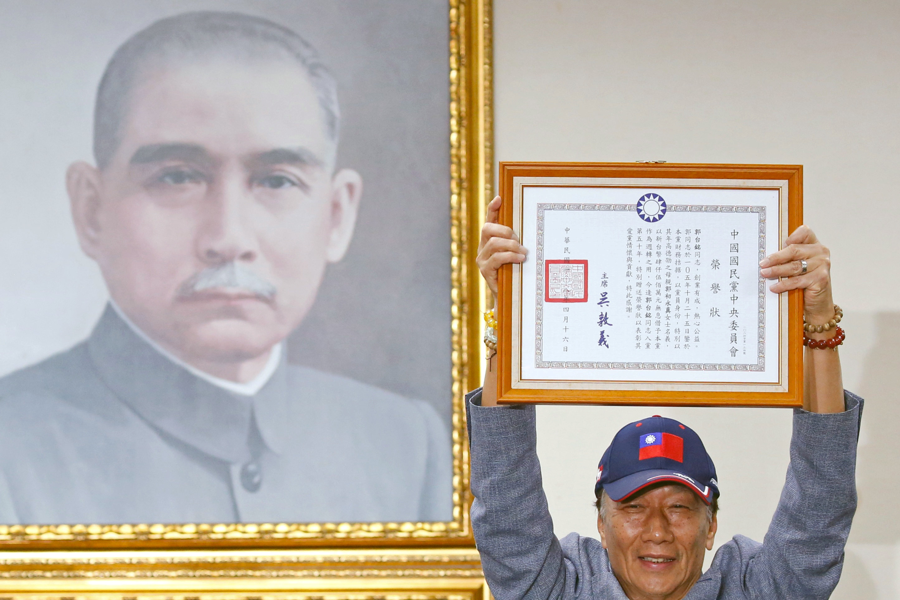 Terry Gou, founder of Foxconn, holds a testimonial next to a portrait of Sun Yat-sen, the founding father of Taiwan, as he announces his bid for the nomination of  the opposition Kuomintang party to run for the island's presidency, in Taipei, Taiwan,...