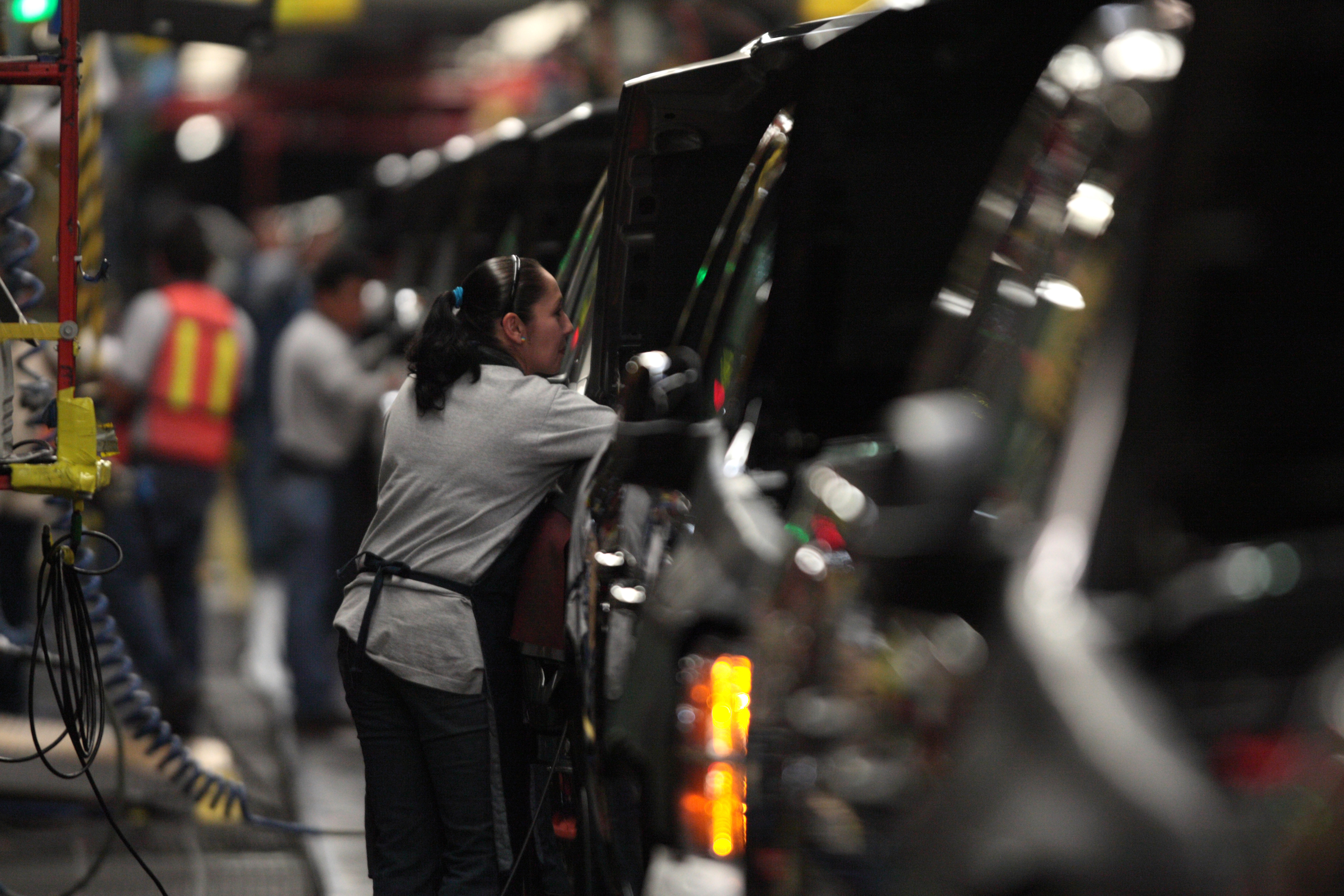 FILE - Factory employees are seen working in the plant of General Motors in the city of Silao, in the state of Guanajuato, Mexico, Nov. 25, 2008.