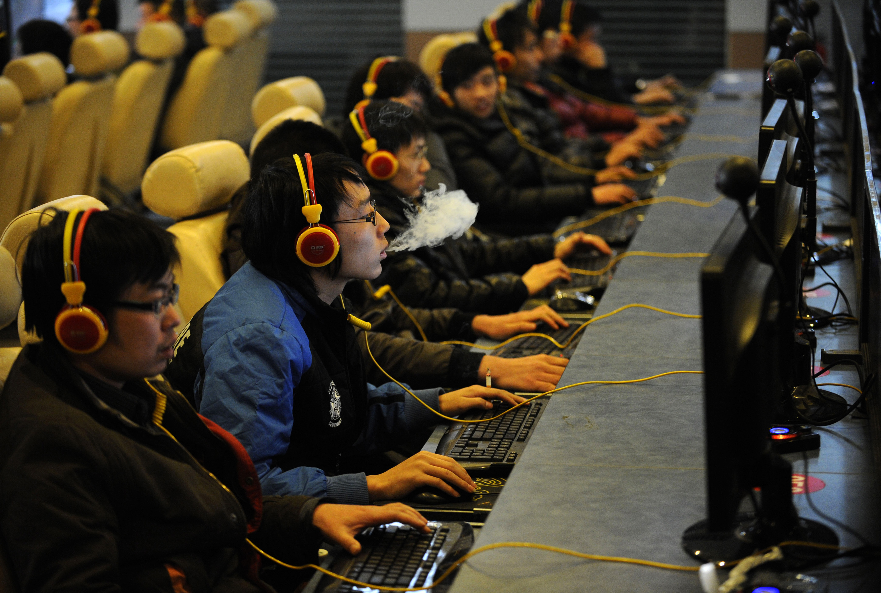 FILE - A man smokes while using a computer at an internet cafe in Taiyuan, Shanxi province, Dec. 30, 2010.