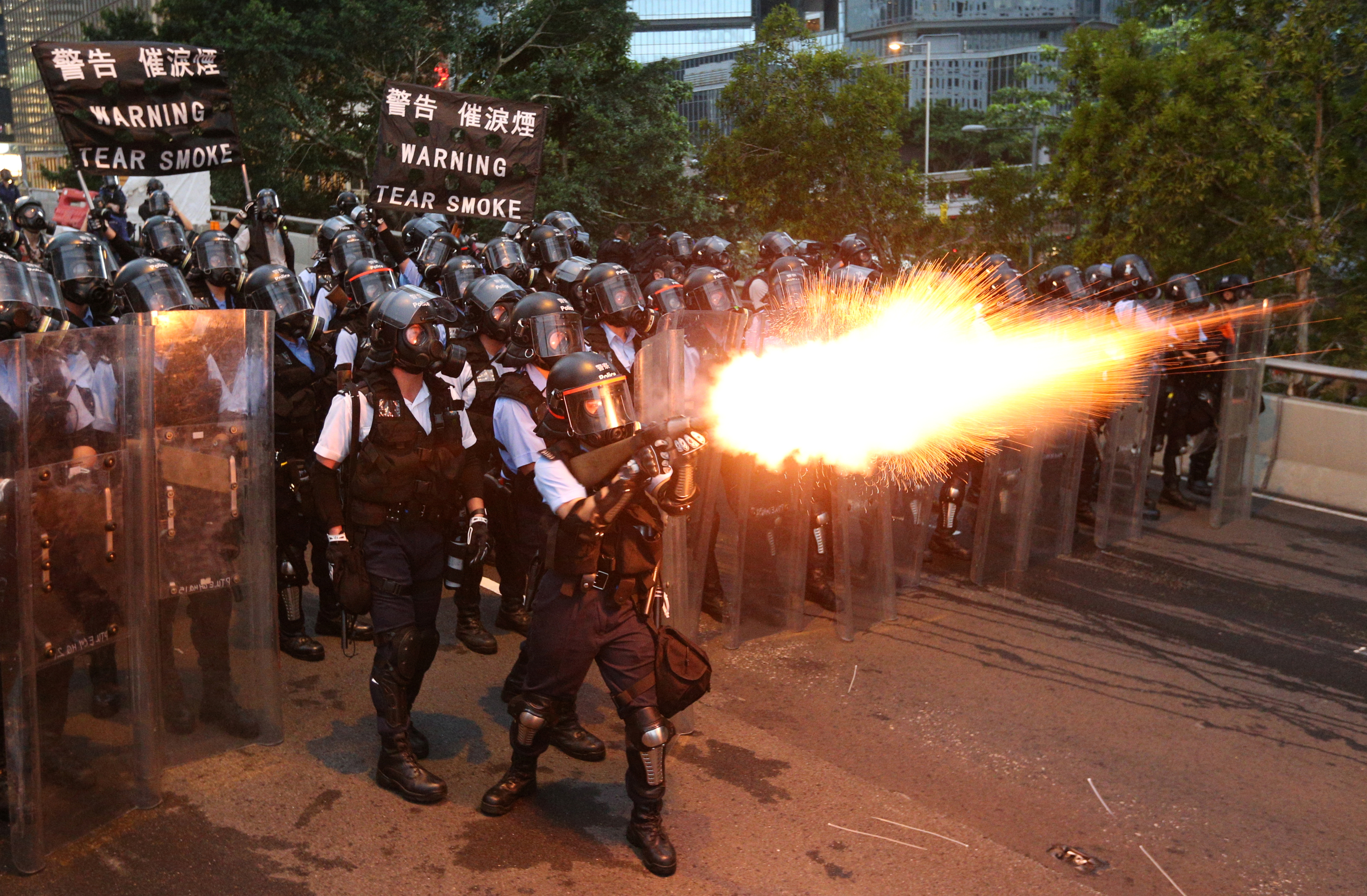 Police officers fire a tear gas during a demonstration against a proposed extradition bill in Hong Kong, June 12, 2019.