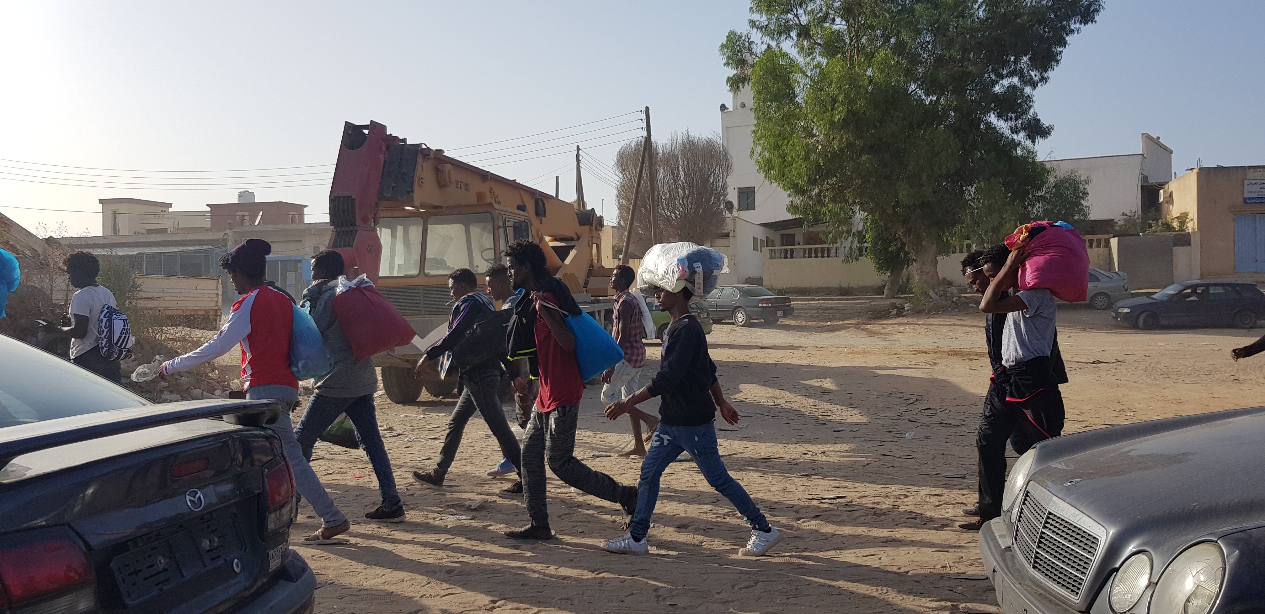 Migrants march towards the offices of international organizations to demand help traveling to Europe after Libyan police agreed to meet their demand for release from the bombed-out facility, in Tripoli, Libya, July 9, 2019. (H.Murdock/VOA)