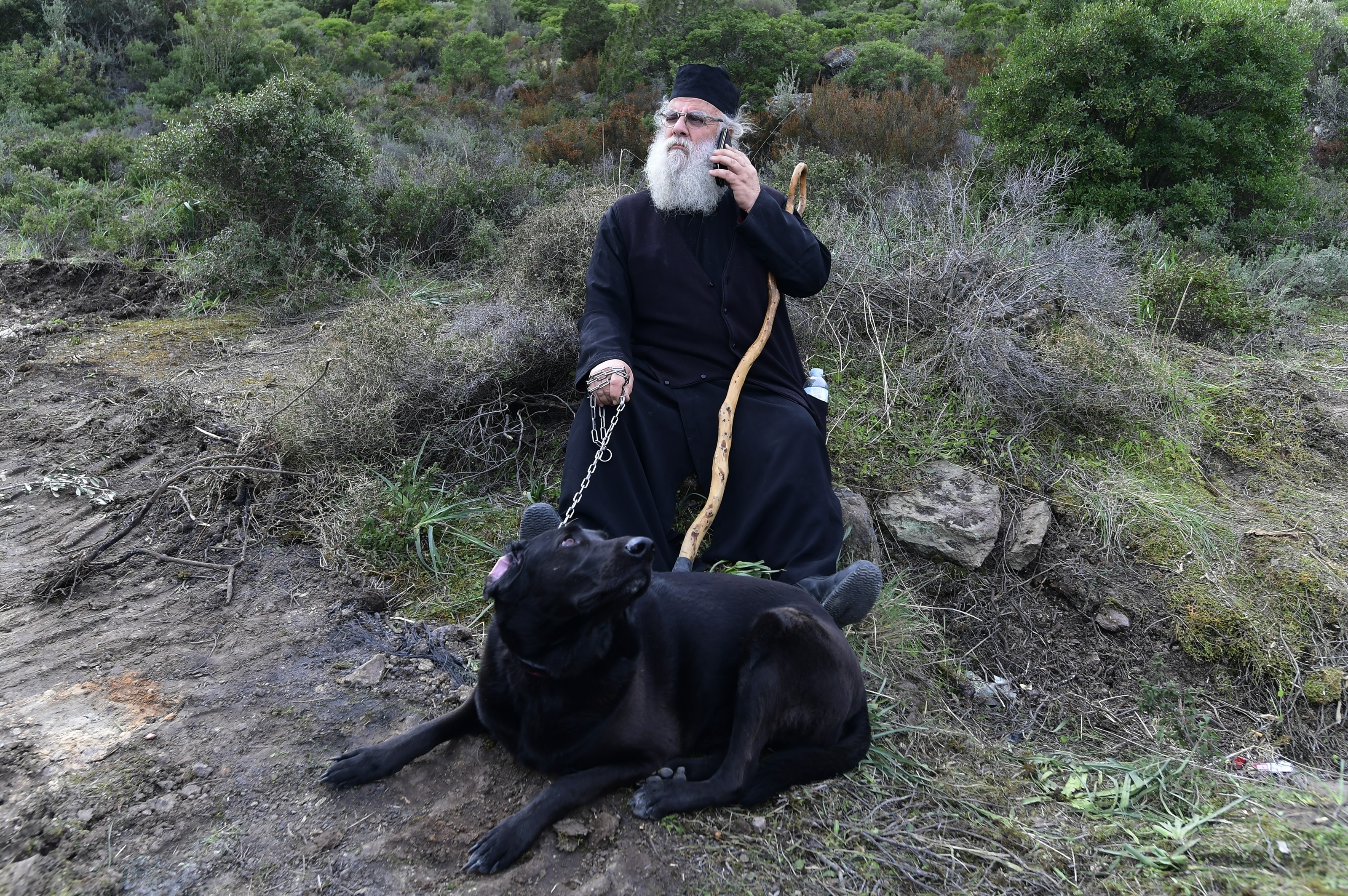 A Greek Orthodox priest speaks on his cellphone as he holds a dog at a roadblock in Karava, on the northeastern Aegean island of Lesbos.