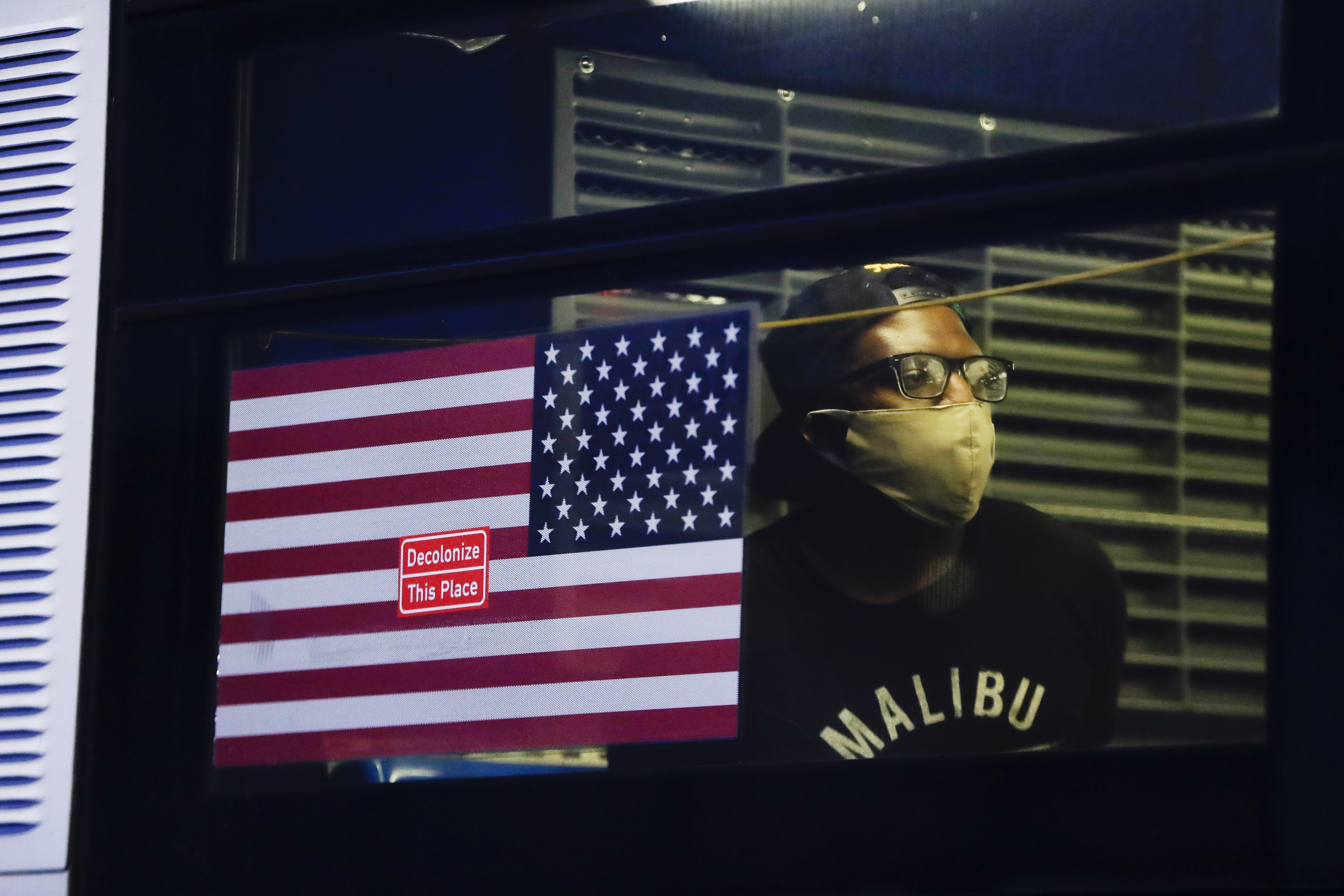 A protester who was arrested waits in the back of a bus during a rally at the Barclays Center over the death of George Floyd, a…