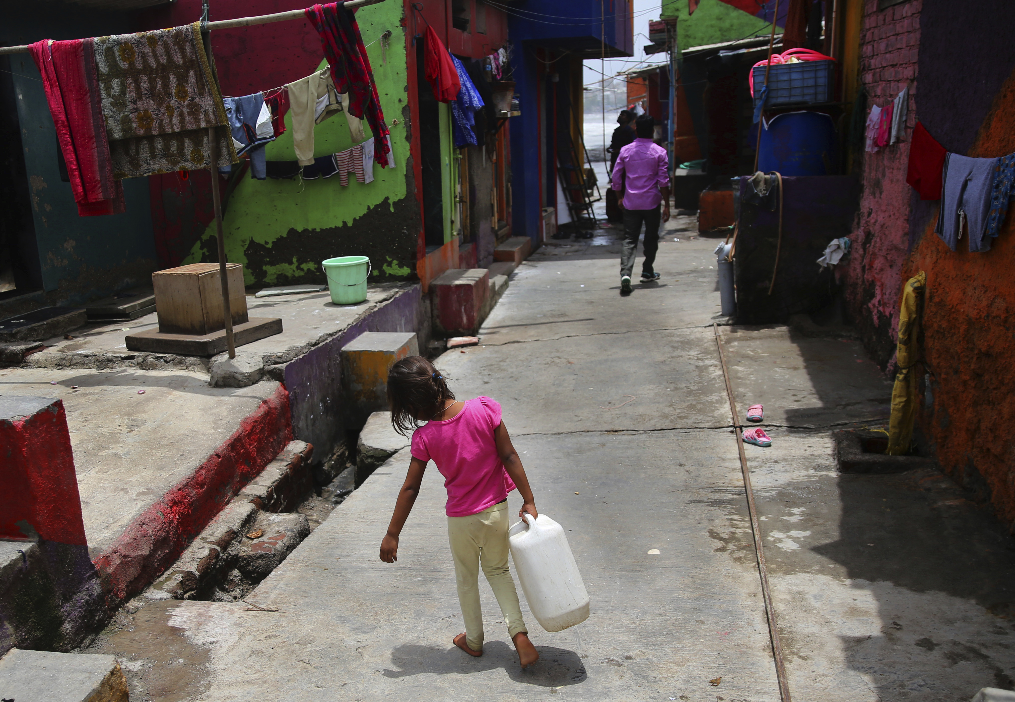 A girl walks carrying drinking water at a slum in Mumbai, India, Wednesday, June 19, 2019. India is facing a 43% deficiency on monsoon rains across the country by its late arrival by a week in June, according to India Meteorological Department…