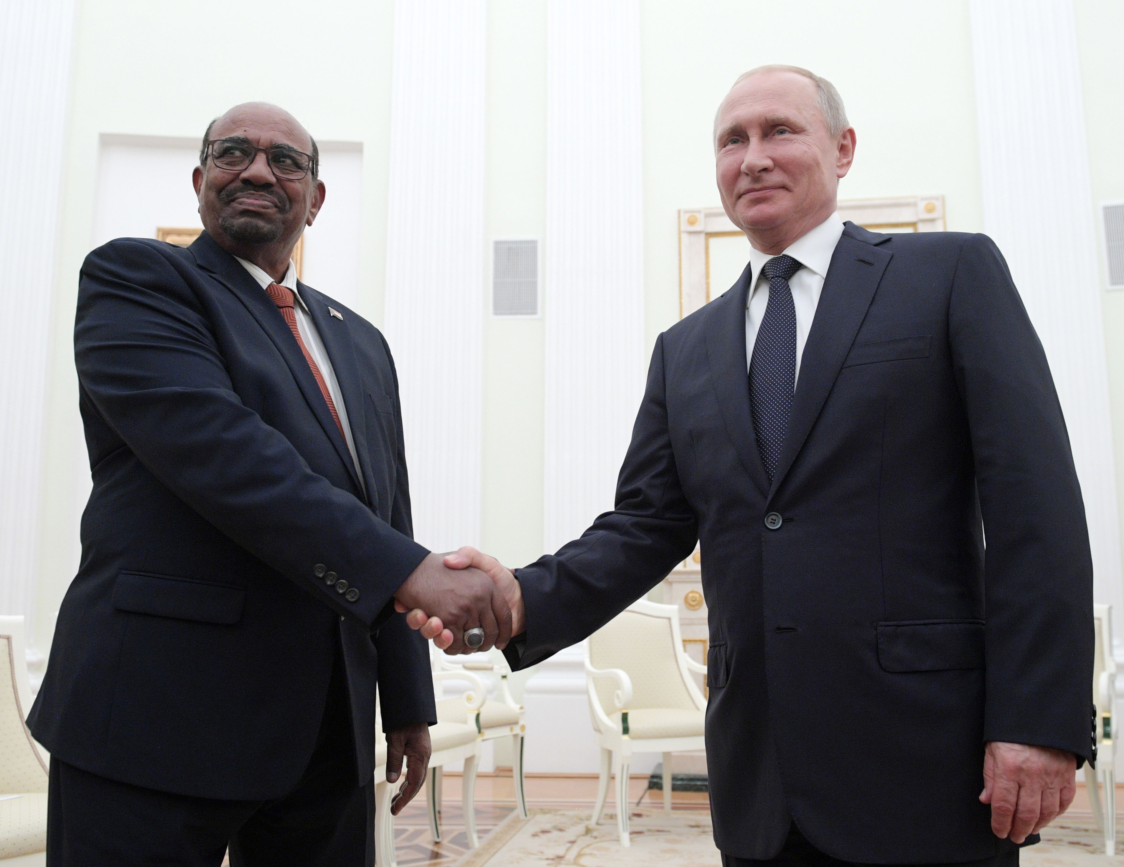 Russian President Vladimir Putin, right, shakes hands with Sudan's President Omar al-Bashir during their meeting in the Kremlin in Moscow, Russia, Saturday, July 14, 2018.