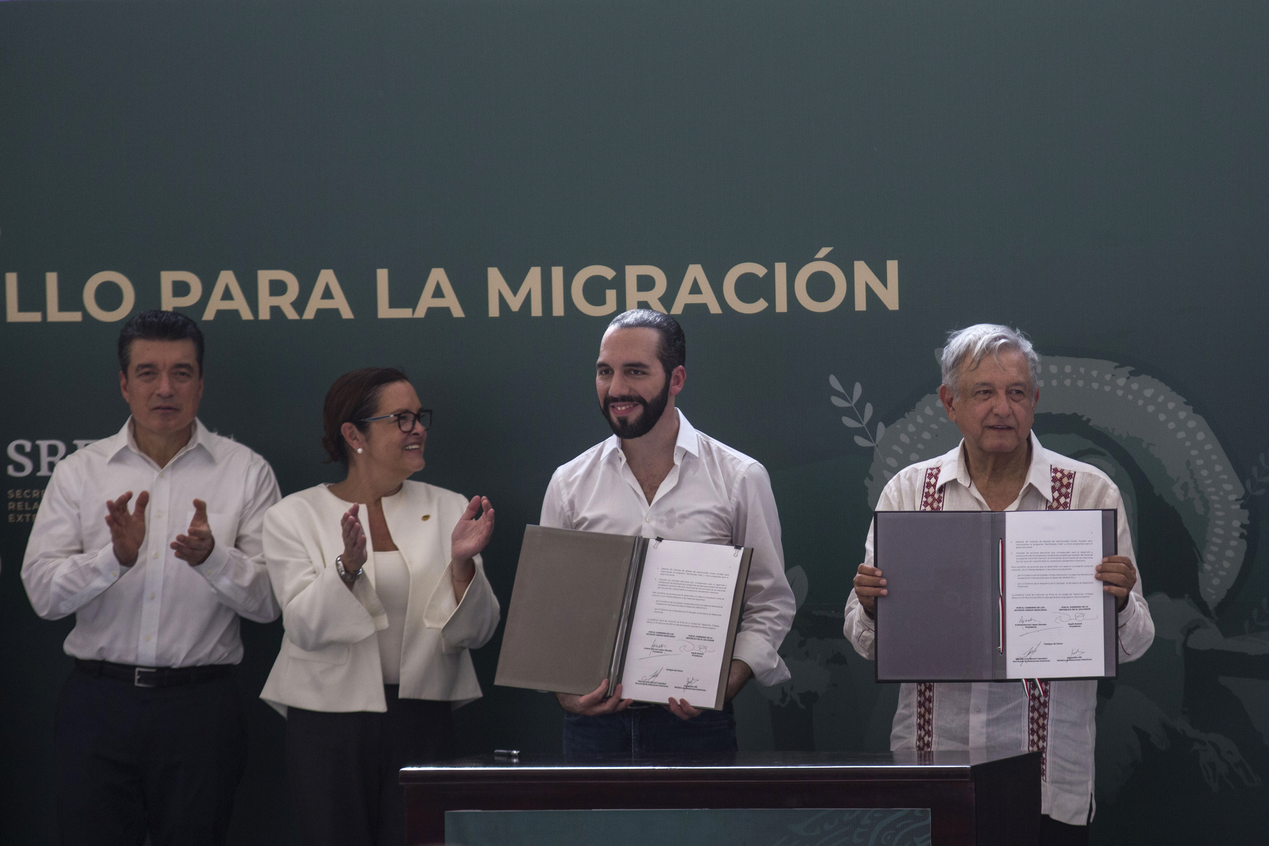 El Salvador's President Nayib Bukele, second from right, and Mexican President Andres Manuel Lopez Obrador, right, show their signed agreements in the border town of Tapachula, Mexico, Thursday, June 20, 2019, as Chiapas Gov. Rutilio Escandon, left,…