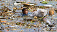 A boy swims as he collects recyclable plastic bottles drifting with garbage along the coast of Manila Bay at the slum area in the Baseco Compound in metro Manila, Philippines October 16, 2017.