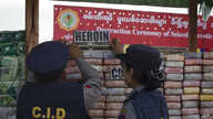 FILE - Myanmar police officers inspect seized drugs during a destruction ceremony of seized narcotic drugs on the outskirts of Yangon, Myanmar, Monday, June 26, 2017.