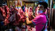 A vendor sells meat at Khlong Toei wet market despite fears of the spread of the COVID-19 coronavirus in Bangkok on April 14,…