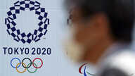 FILE - A man wearing a face mask walks passed a billboard with the logo of the Tokyo 2020 Olympics, in Tokyo, Japan, April 2, 2020.