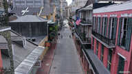 FILE - The normally bustling tourist mecca of Bourbon Street lies deserted in the early afternoon during shelter in place orders to slow the spread of the coronavirus, in New Orleans, Louisiana, March 27, 2020.