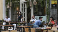 A waitress wearing a protective facemask and plastic gloves serves coffee at a cafe in central Athens on May 25, 2020, as cafes…
