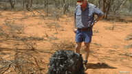 Australian farmer James Stirton stands next to a ball of twisted metal, purported to be fallen space junk, on his farm in…