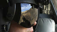The Afghan mountains are reflected in the visor of a US Army Airborne CH-47 Chinook window gunner