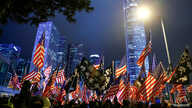 Protestors hold U.S. flags during a gathering at the Edinburgh place in Hong Kong, China, November 28, 2019. REUTERS/Thomas…