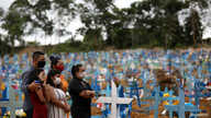 Relatives are seen during a mass burial of people who passed away due to the coronavirus disease (COVID-19), at the Parque…