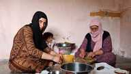 Ismahan, left, and her mother make traditional food using leaves plucked from trees, because they cannot afford to buy them, in Istanbul, May 20, 2020. (VOA/Heather Murdock).