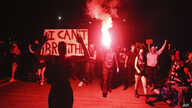 In this May 29, 2020, photo, Portlanders march with flares from the George Floyd vigil at Peninsula Park towards the Justice…