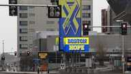 A usually busy Summer Street runs past signs for the Boston Hope field hospital at the Convention Center, during the…